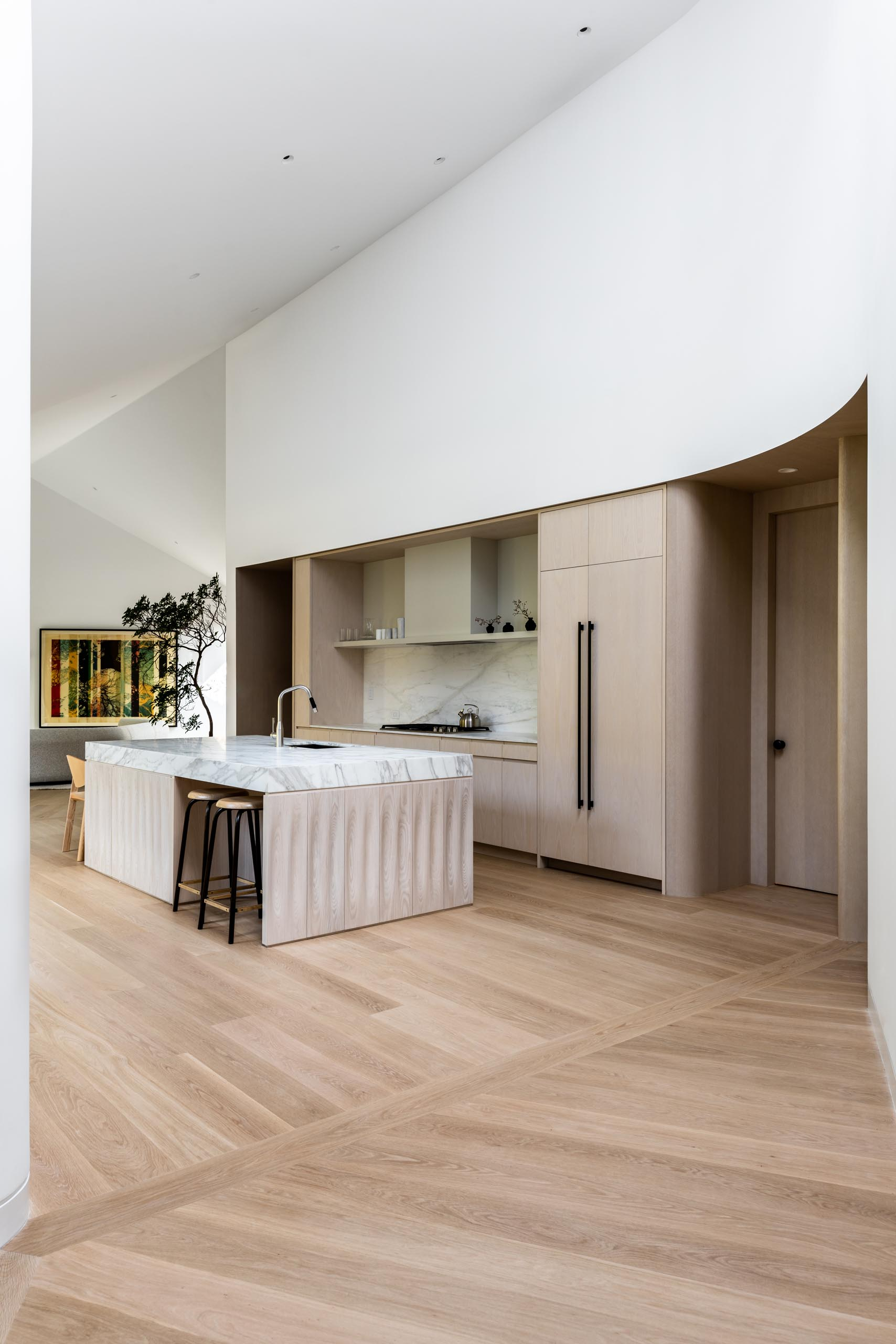 Not only does the kitchen have minimalist wood cabinets with black hardware, but the island has a thick countertop made from light marble.