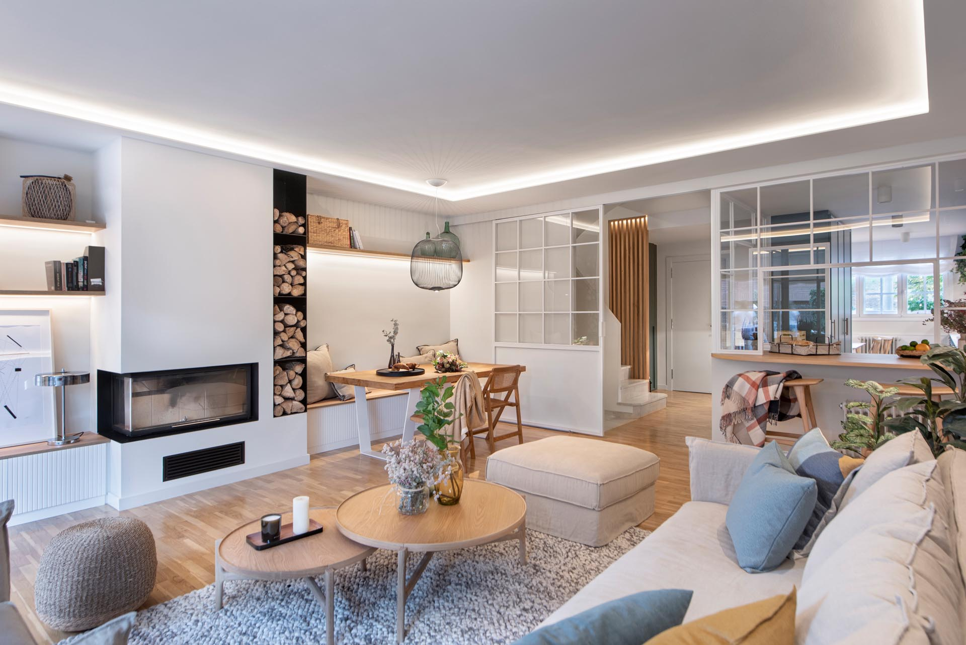 This modern open plan living room has shelving that lines the wall, while the couch and armchair are focused on the fireplace and built-in firewood storage.