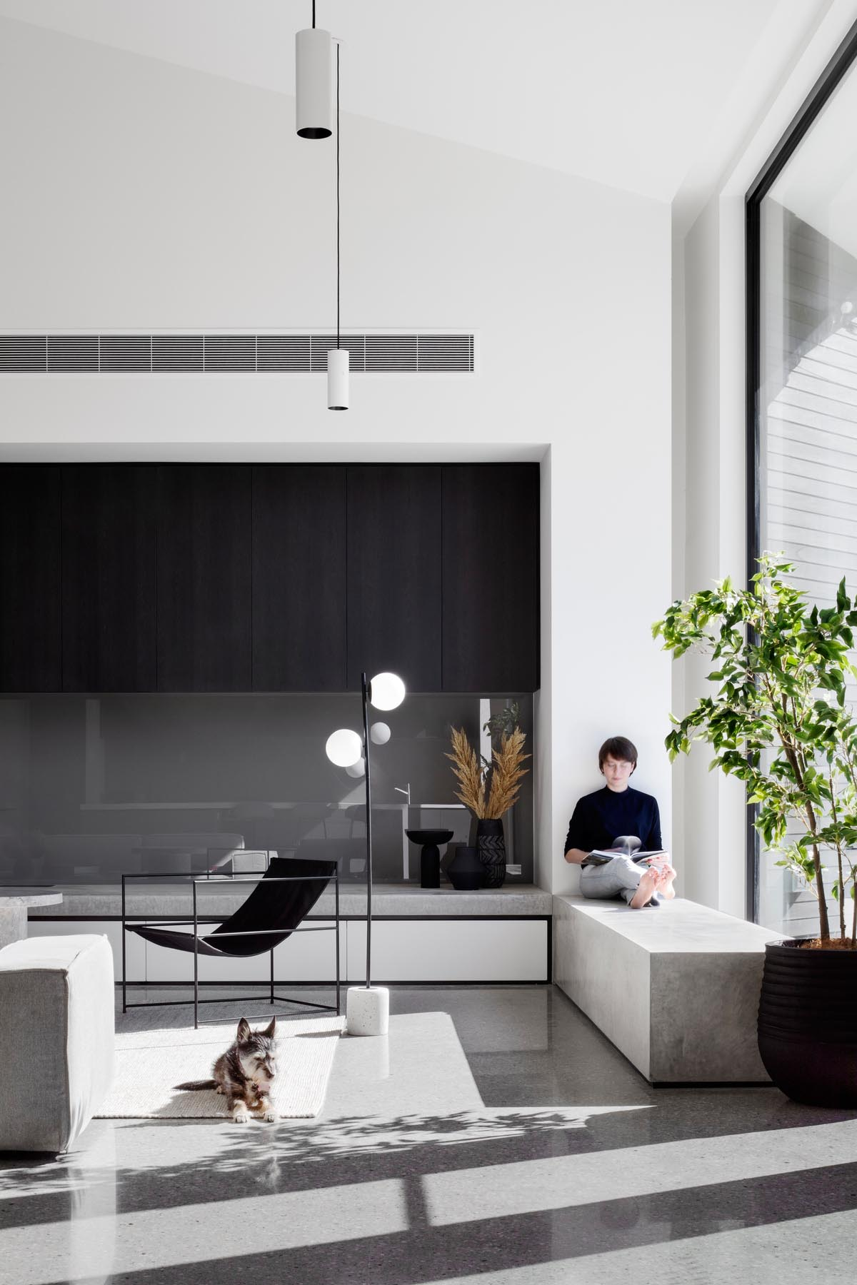 This modern living room has a minimalist fireplace and a concrete window bench by a large window.