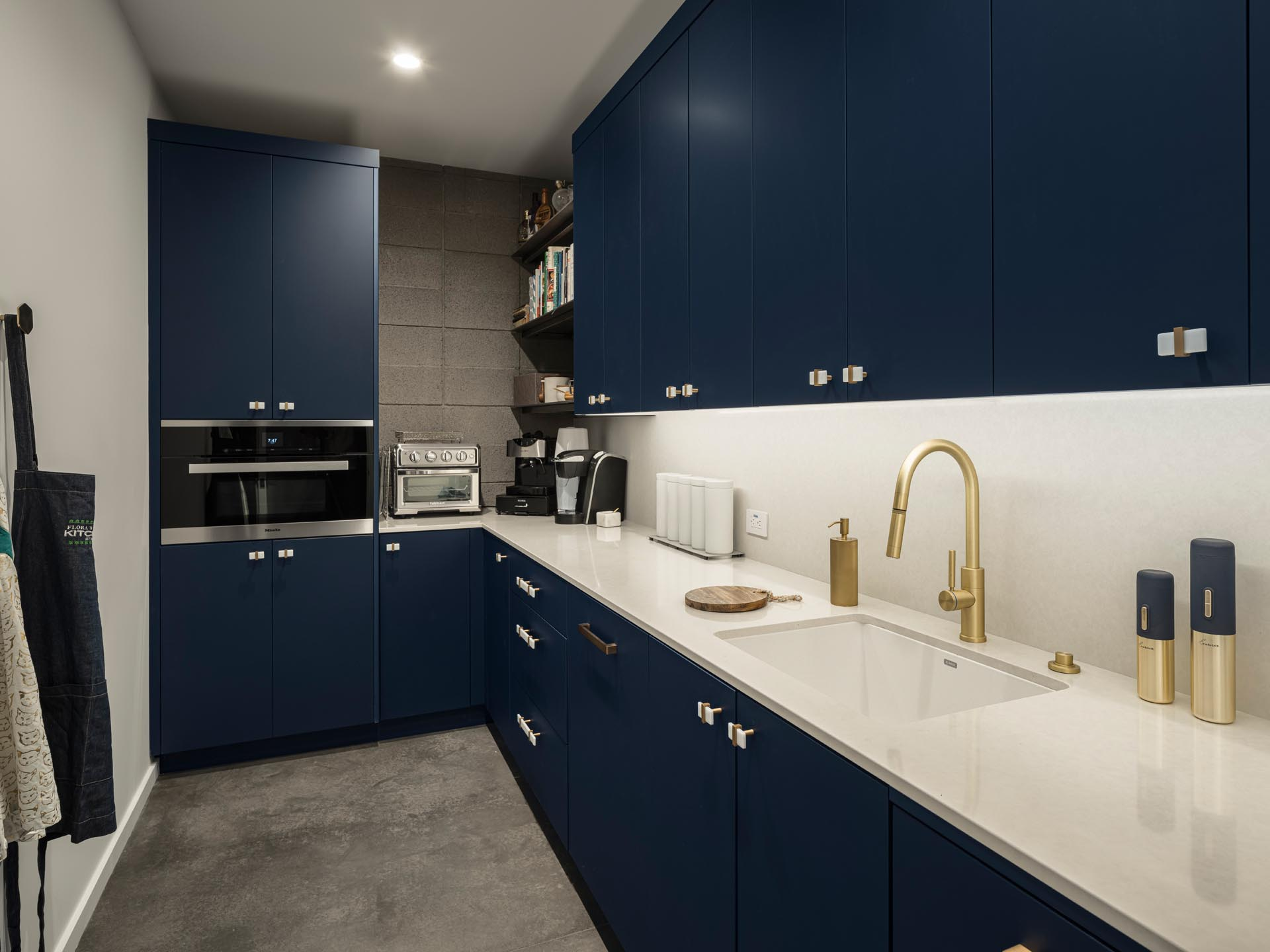 A large walk-in pantry with dark blue minimalist cabinets, that provide plenty of storage room.