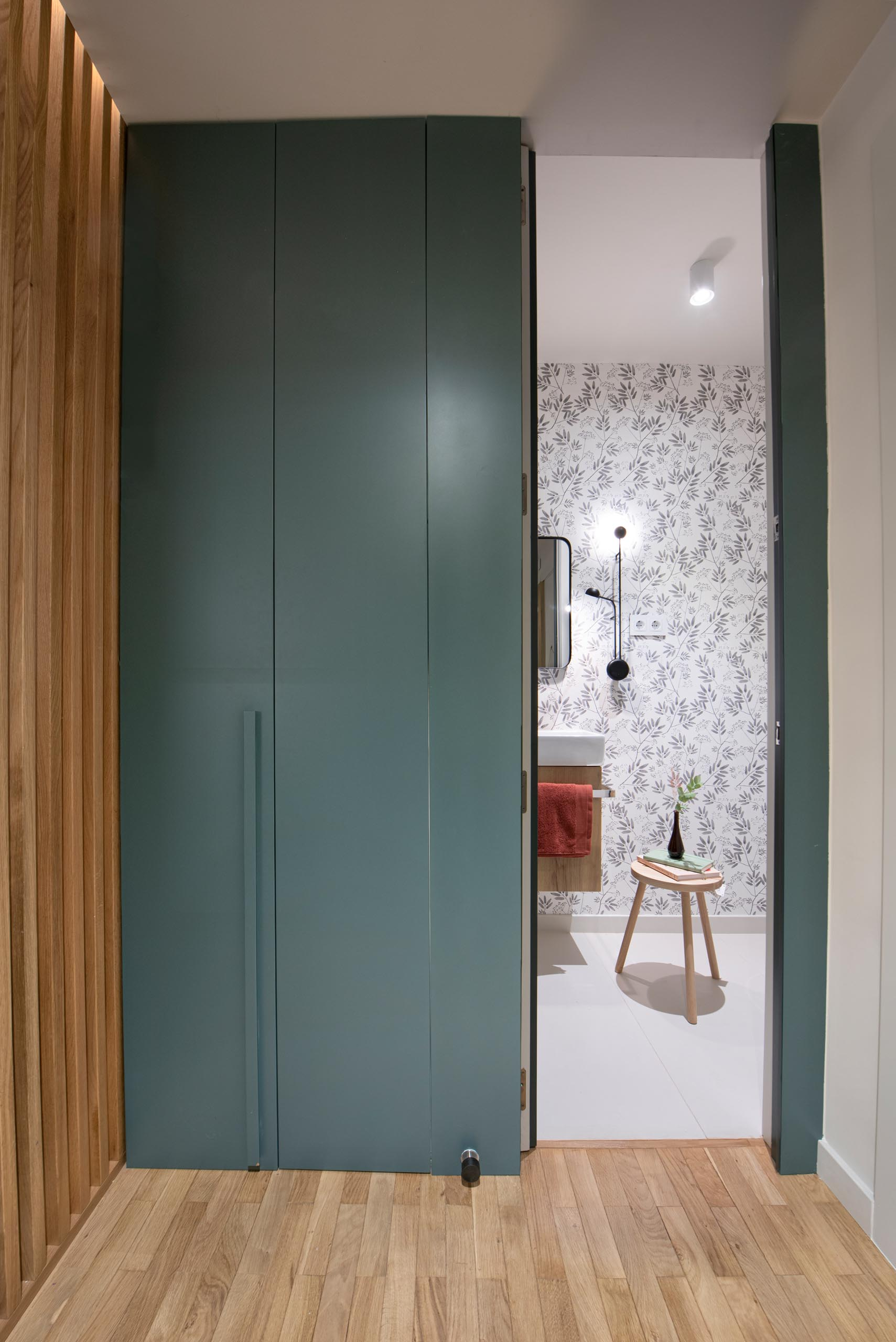 This modern home includes a three-door wardrobe in a eucalyptus green finish, that hides a minimal, functional and attractive powder room