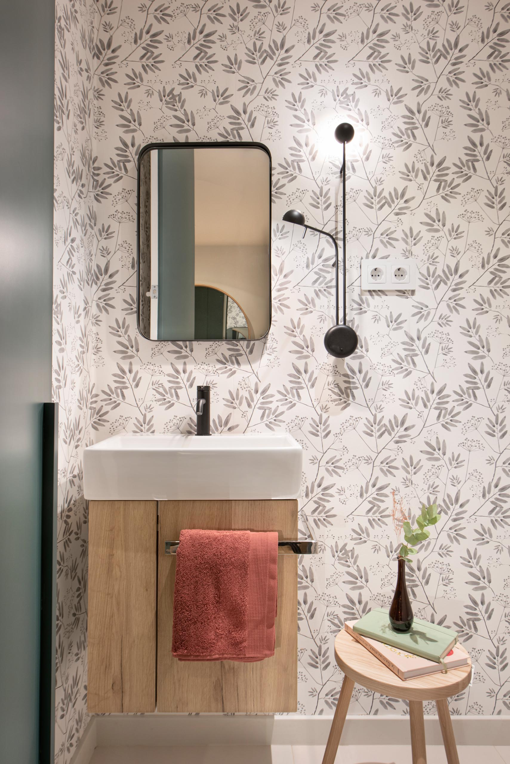 Floral pattern wallpaper, high contrast accessories and taps, and a wall lamp by Ichiro Iwasaki for Vibia, gives this powder room a unique appearance.