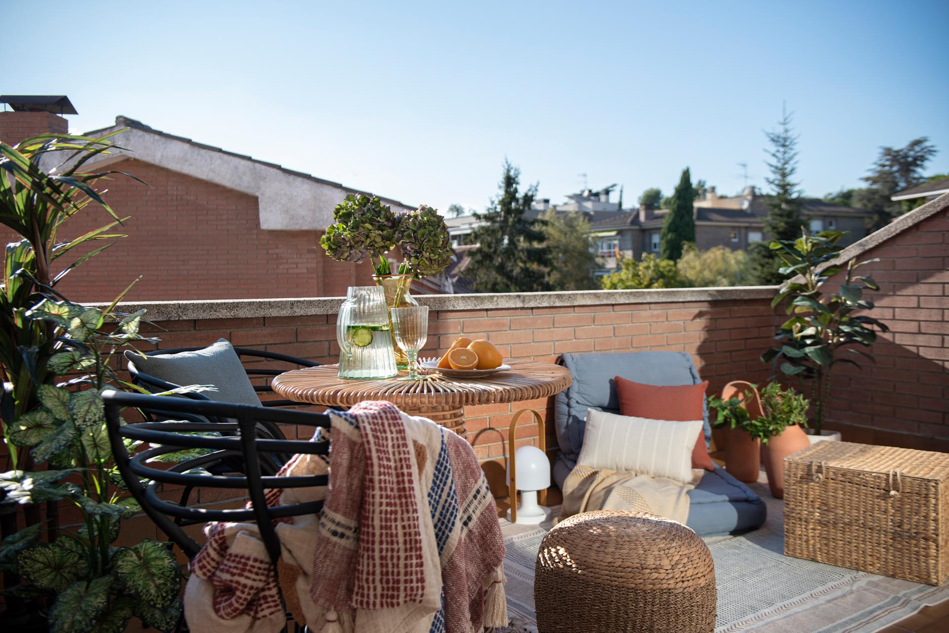 A sliding door opens to a balcony with views of the neighborhood. A small table with chairs, as well as an outdoor rug and low cushion furniture gives the space multiple uses.