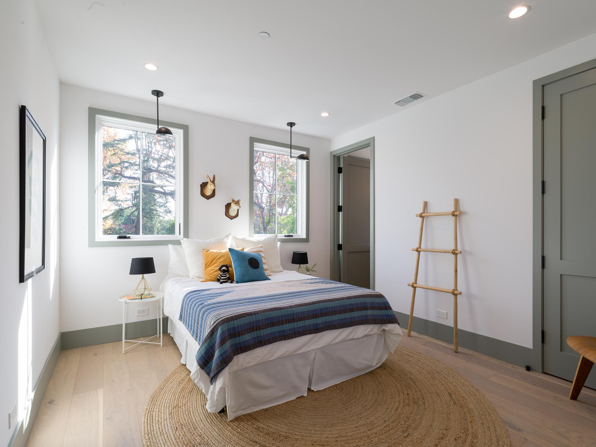 A contemporary bedroom with white walls, wood floors, and gray trim.