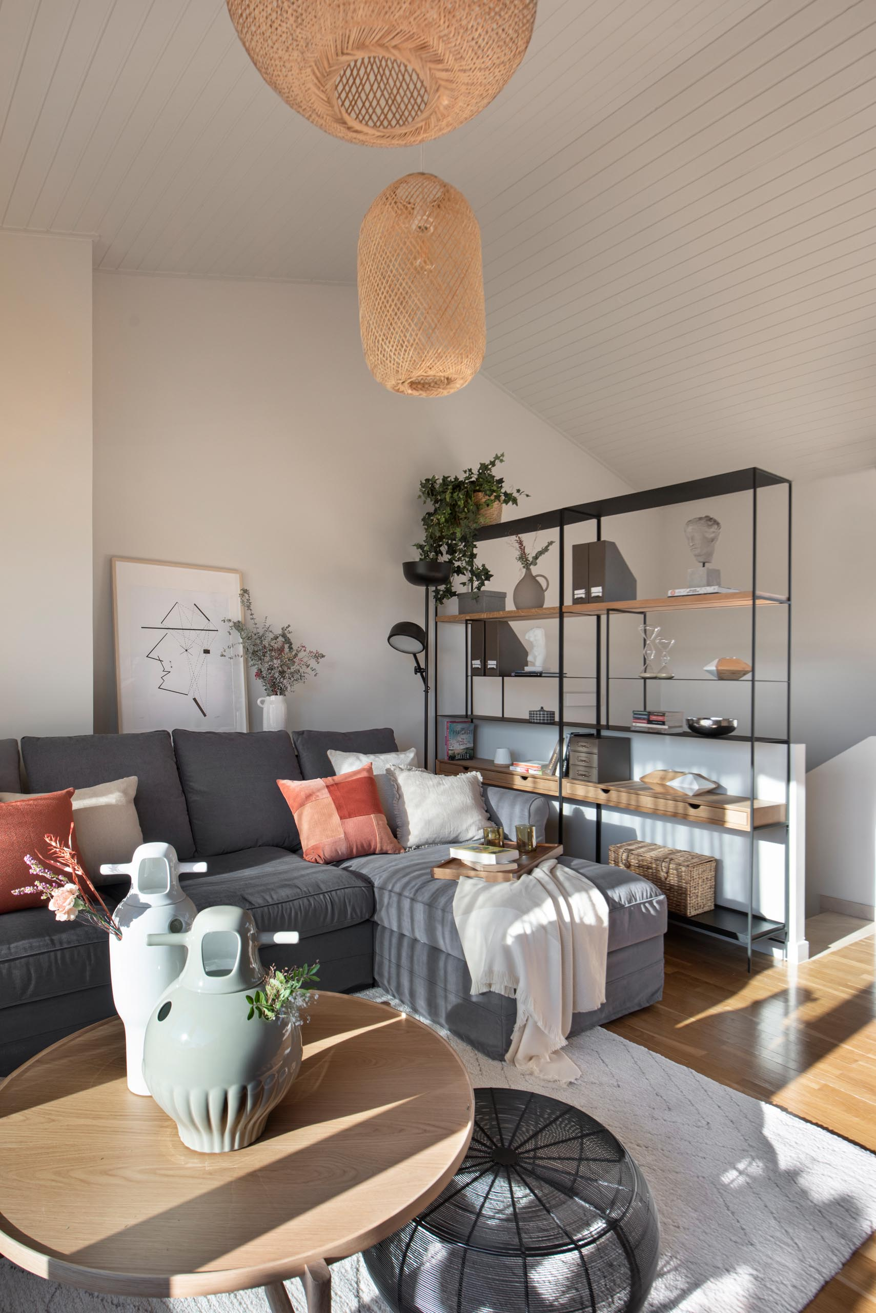 On the top level of this modern home is a secondary living room with a pitched ceiling. The living room is furnished with a couch, shelving unit, rattan pendant lights, a desk with TV above it, and a reading area with built-in shelves.
