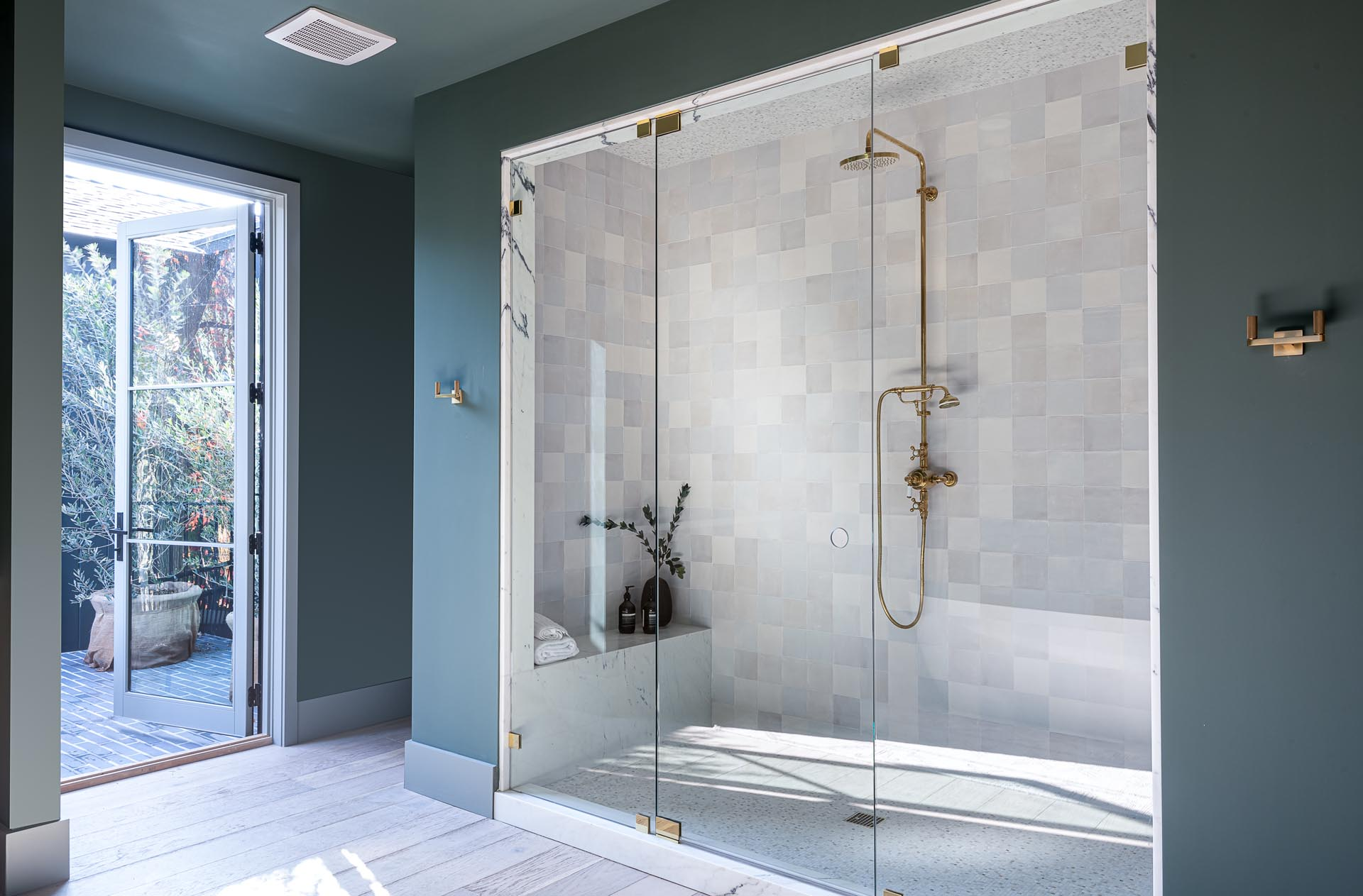 The glass enclosed walk-in shower is lined with square tiles, while a bench has been built-in at one end.