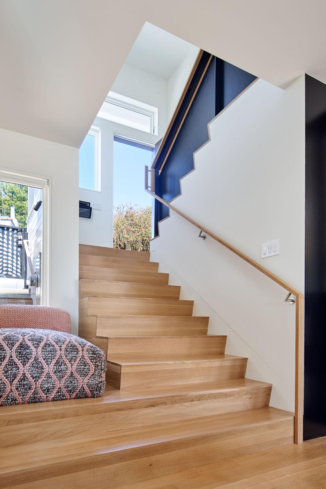 The contemporary entryway and wood stairs of a split-level home.