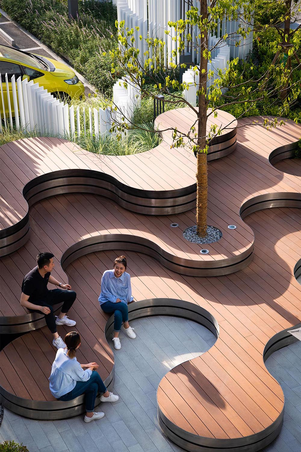 A landscaped park that includes curved tiered seating, a vertical white strip fence, and outdoor lighting.