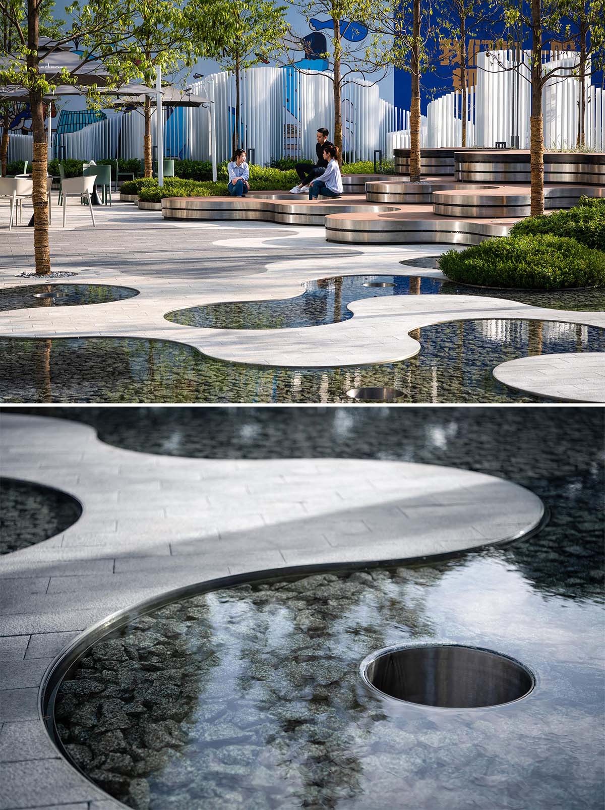 A landscaped park that includes curved tiered seating, water features, and a vertical white strip fence.