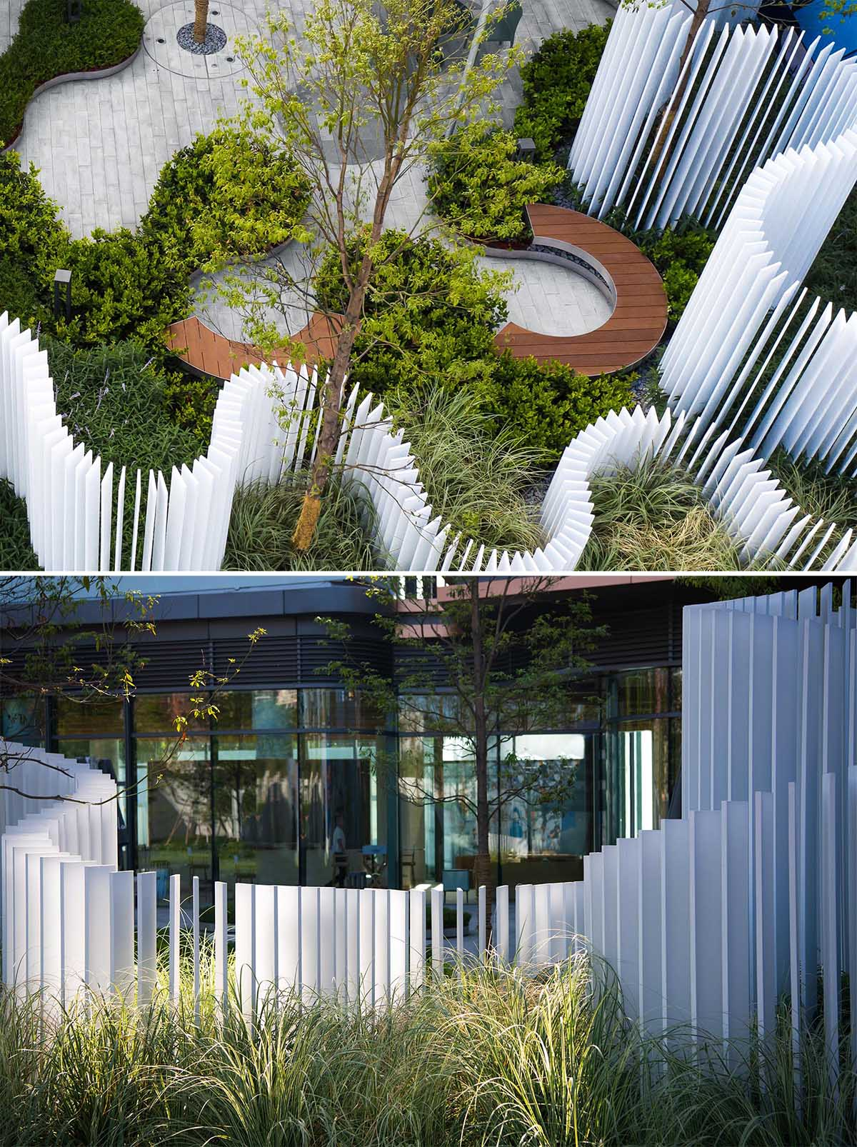 A landscaped park that includes curved seating, and a vertical white strip fence.