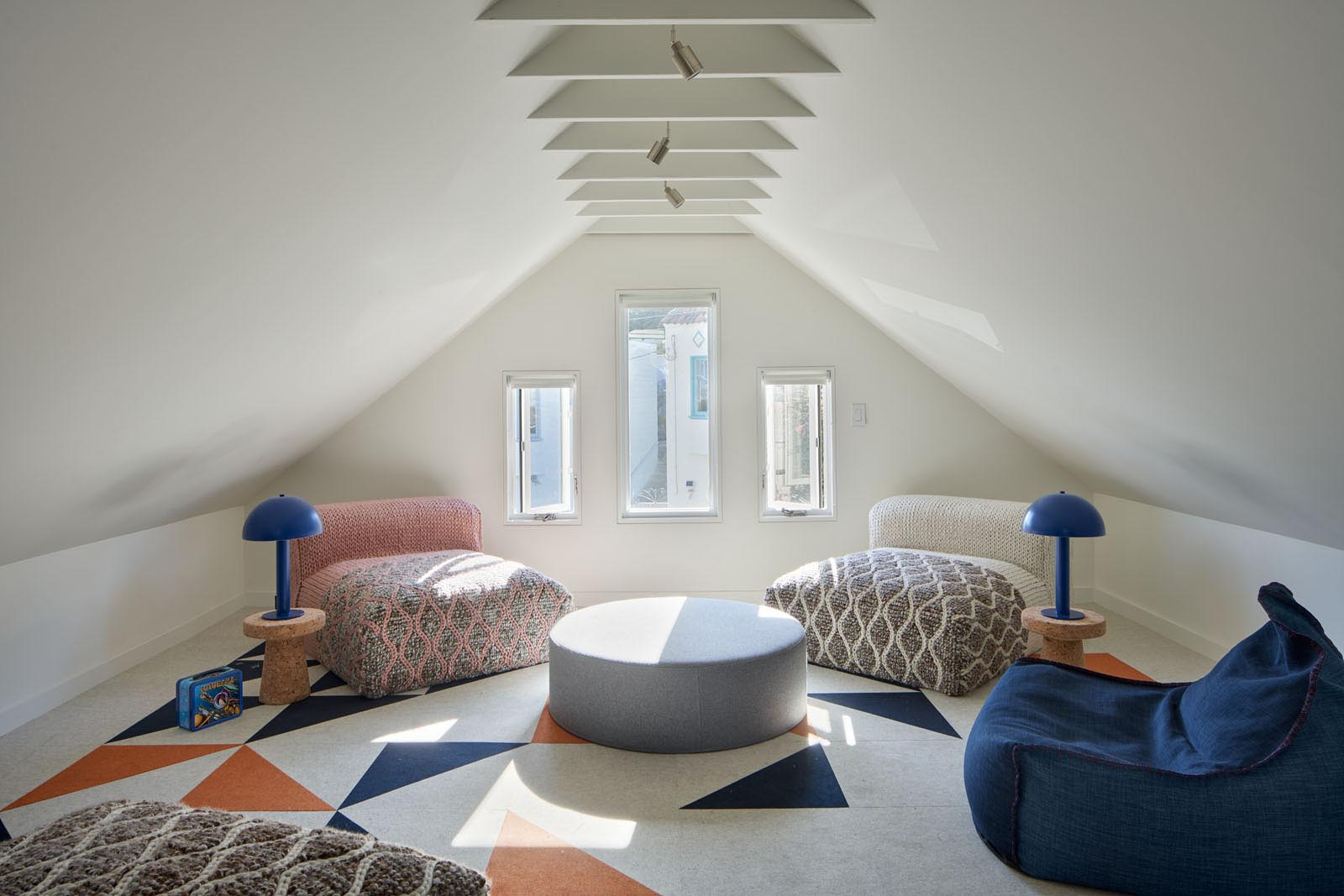 A modern attic that's been furnished with comfortable low chairs, a pair of lights, a rug, and an upholstered round ottoman.