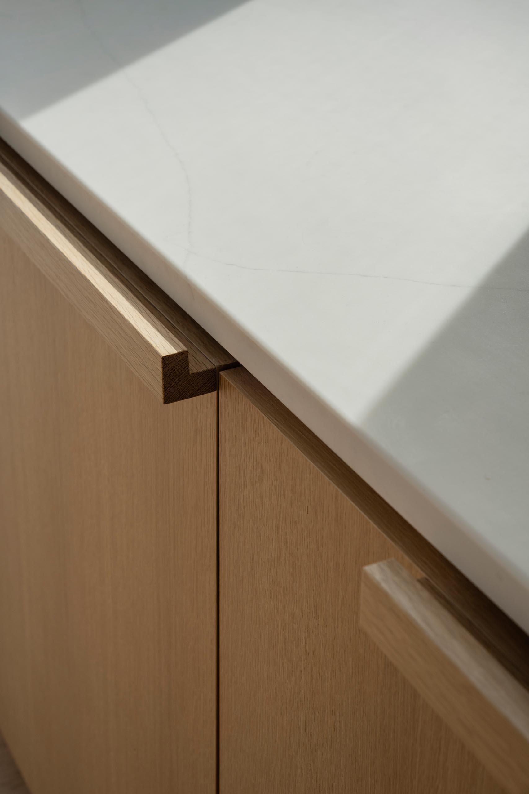 White rift oak kitchen cabinets and quartz countertops.