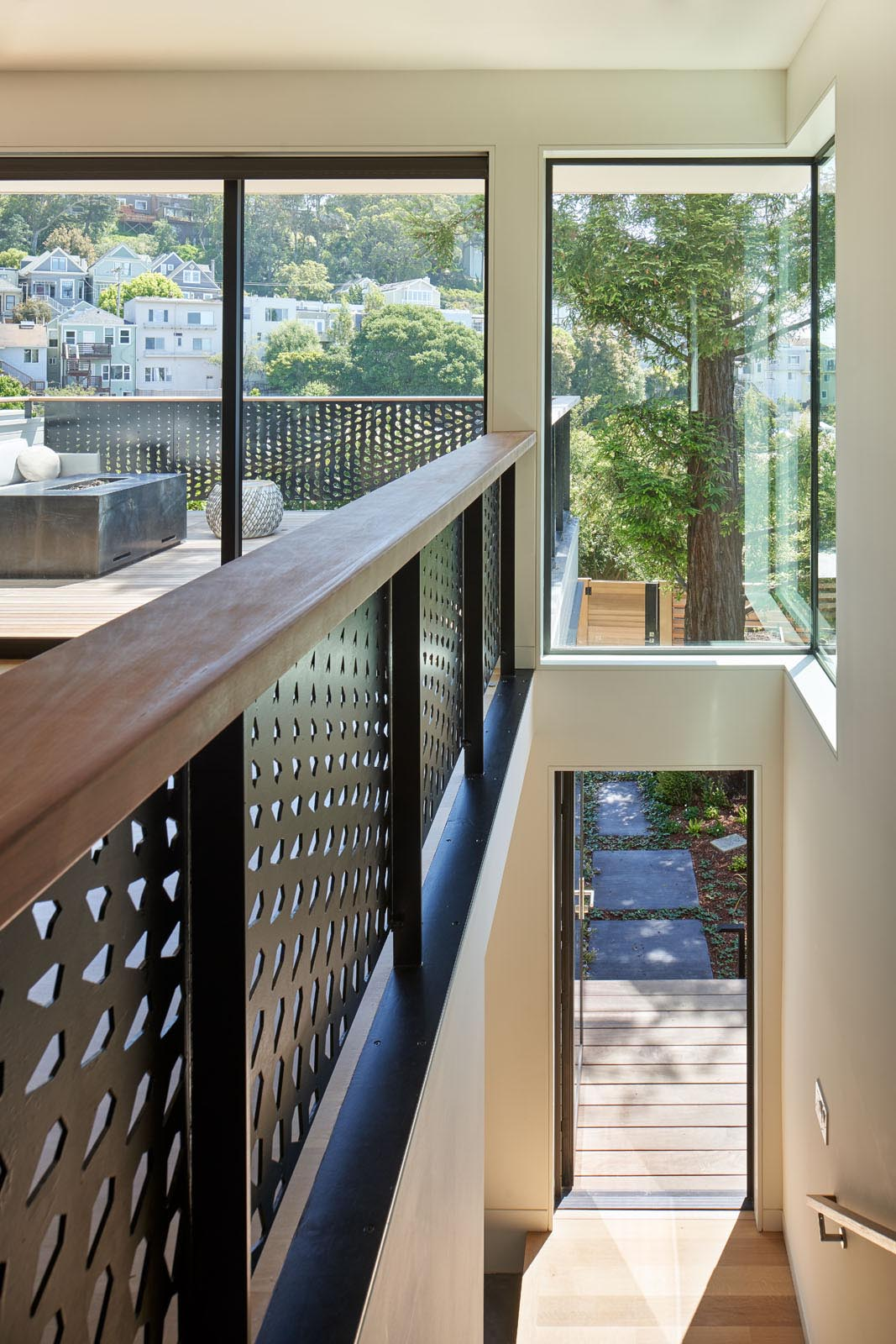 A metal guardrail inspired by the huge conifer tree outside and its pine cones.