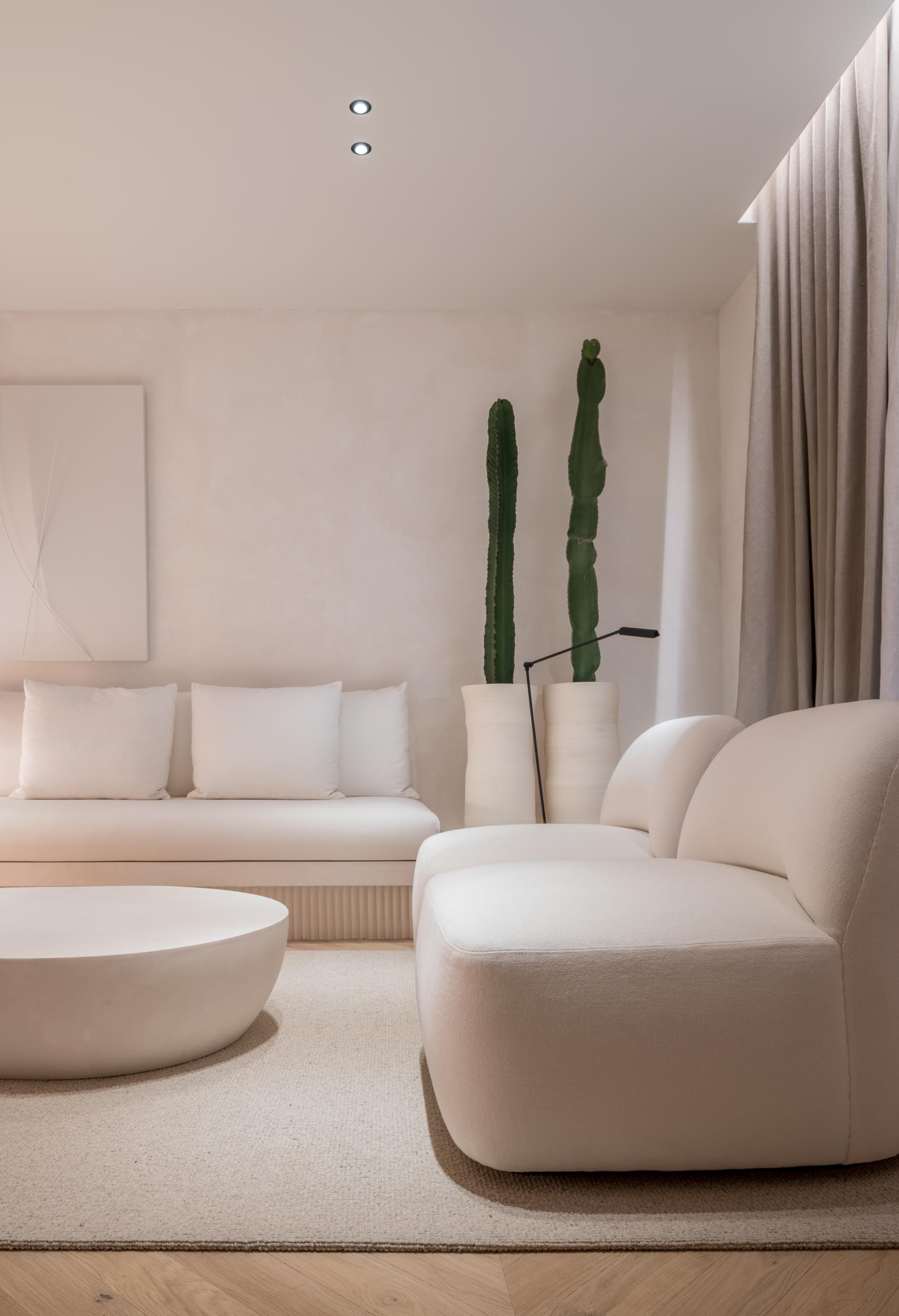 A living room with a simple white color palette, a built-in fireplace, and furniture with curved edges that creates a calm environment with a modern flair.