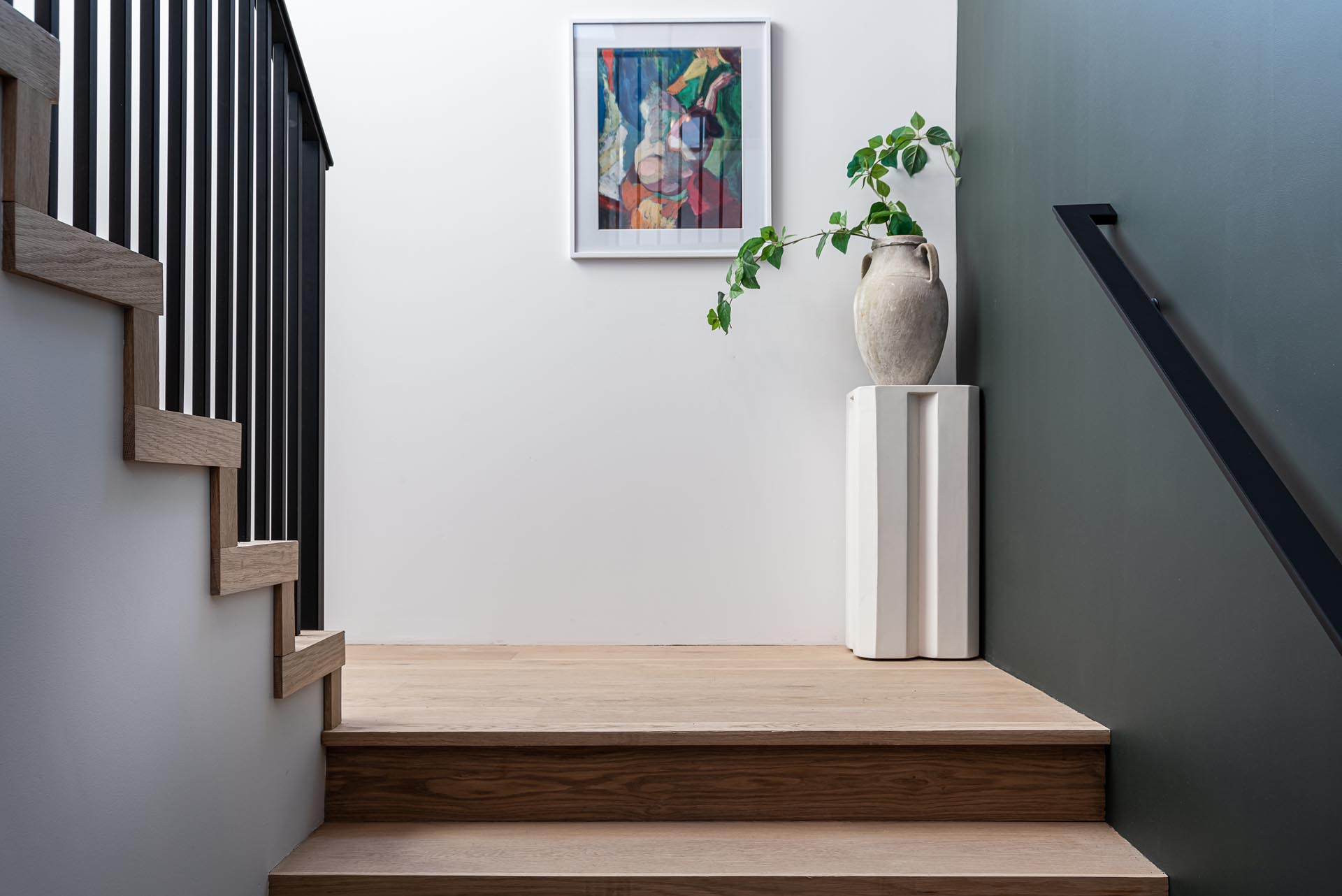 Wood stairs with a black handrail lead to the upper floor of this modern farmhouse inspired home.