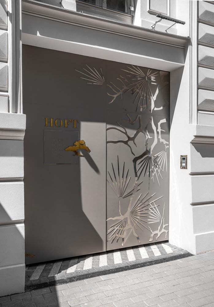 An apartment building door with a tree motif.