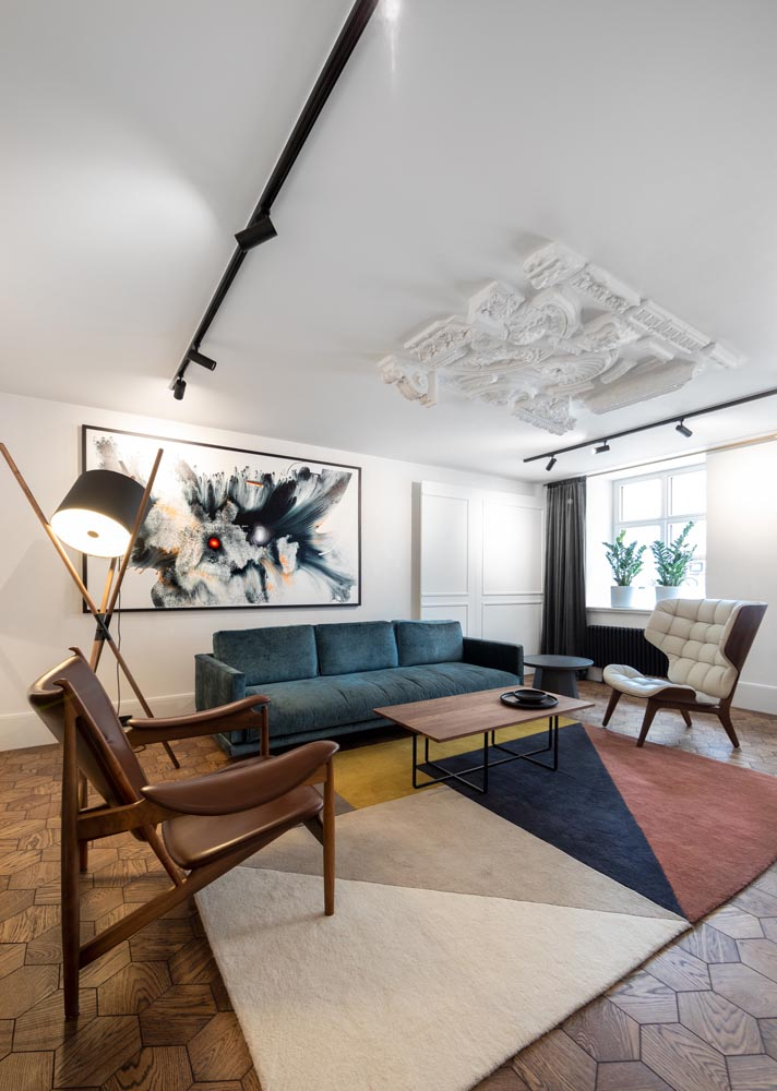 This apartment building common room has been designed with historical touches and modern furnishings, which provide spaces to meet and mingle with other residents.