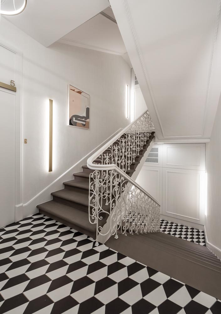 Bold patterned floors create eye-catching black and white elements throughout an apartment building.