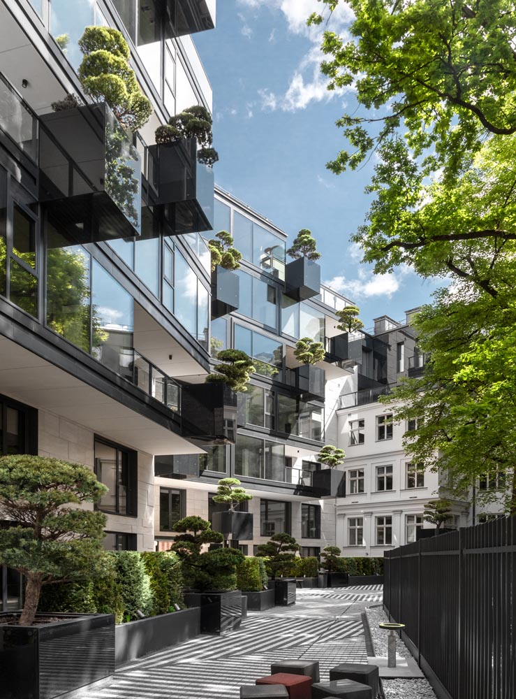 As part of the design of the new facade of this apartment building, 'flying' conifers and bonsai trees were placed in cantilevered planters.