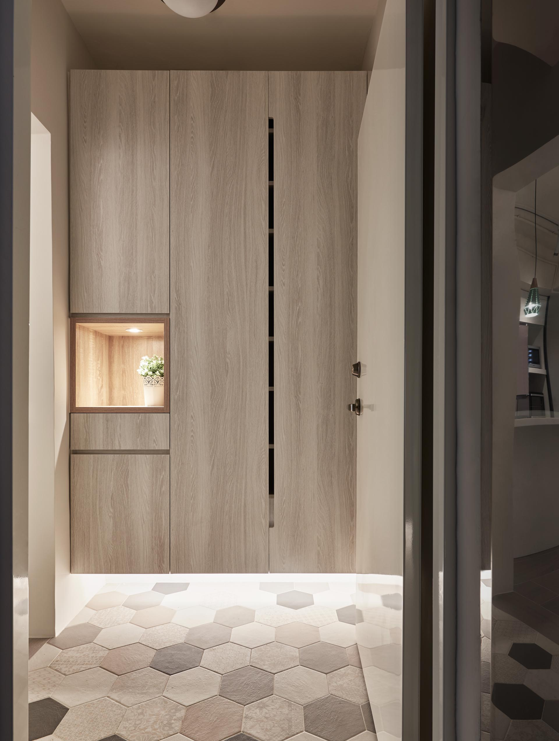 The entryway has tall storage closets that float above a tiled floor, that's highlighted with the use of hidden LED lights. A small open shelf with a light is an ideal place for keys and wallets.