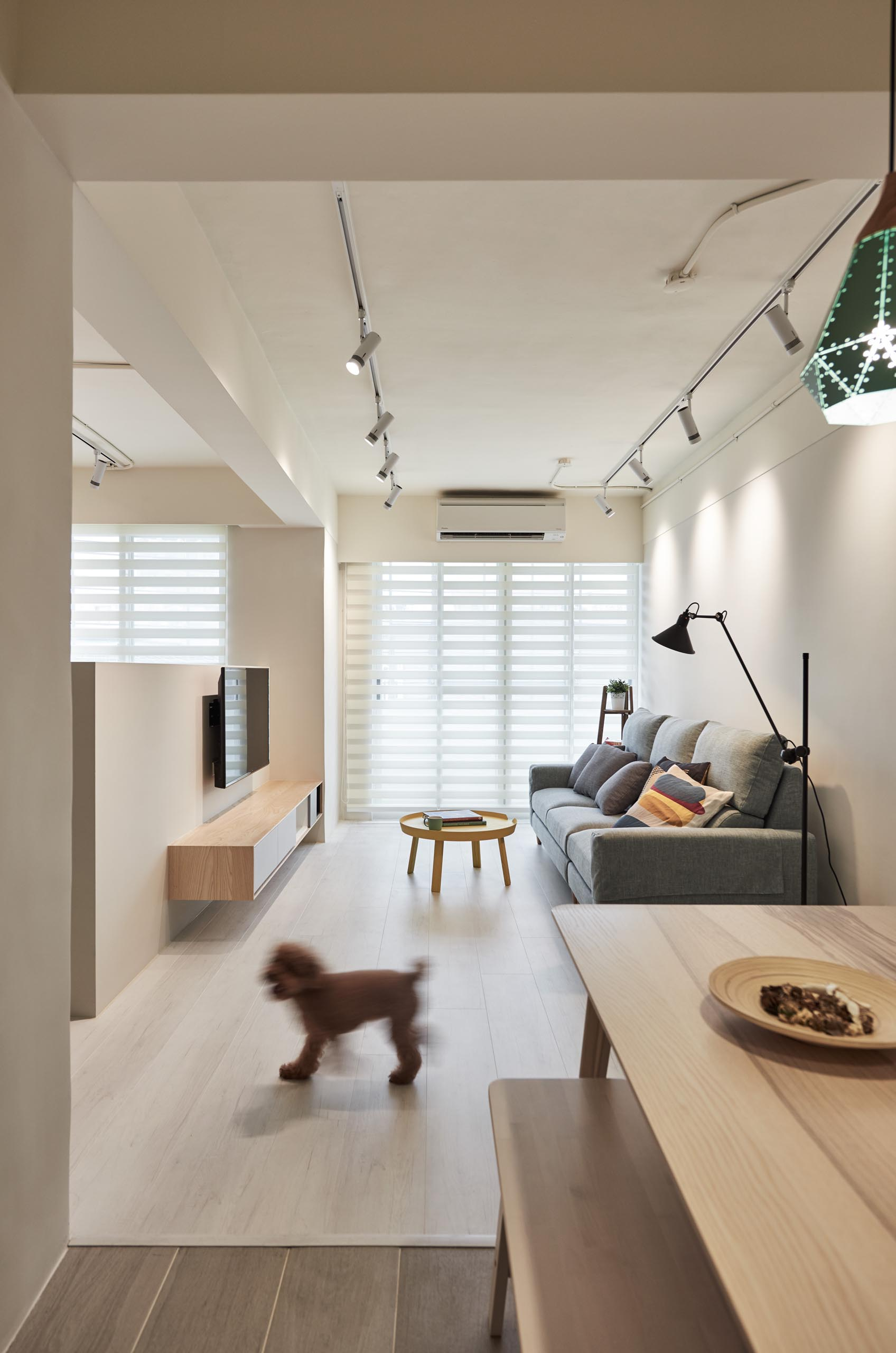 The living room receives an abundance of natural light from the large windows, while track lighting allows light to be directed at different areas of the room.