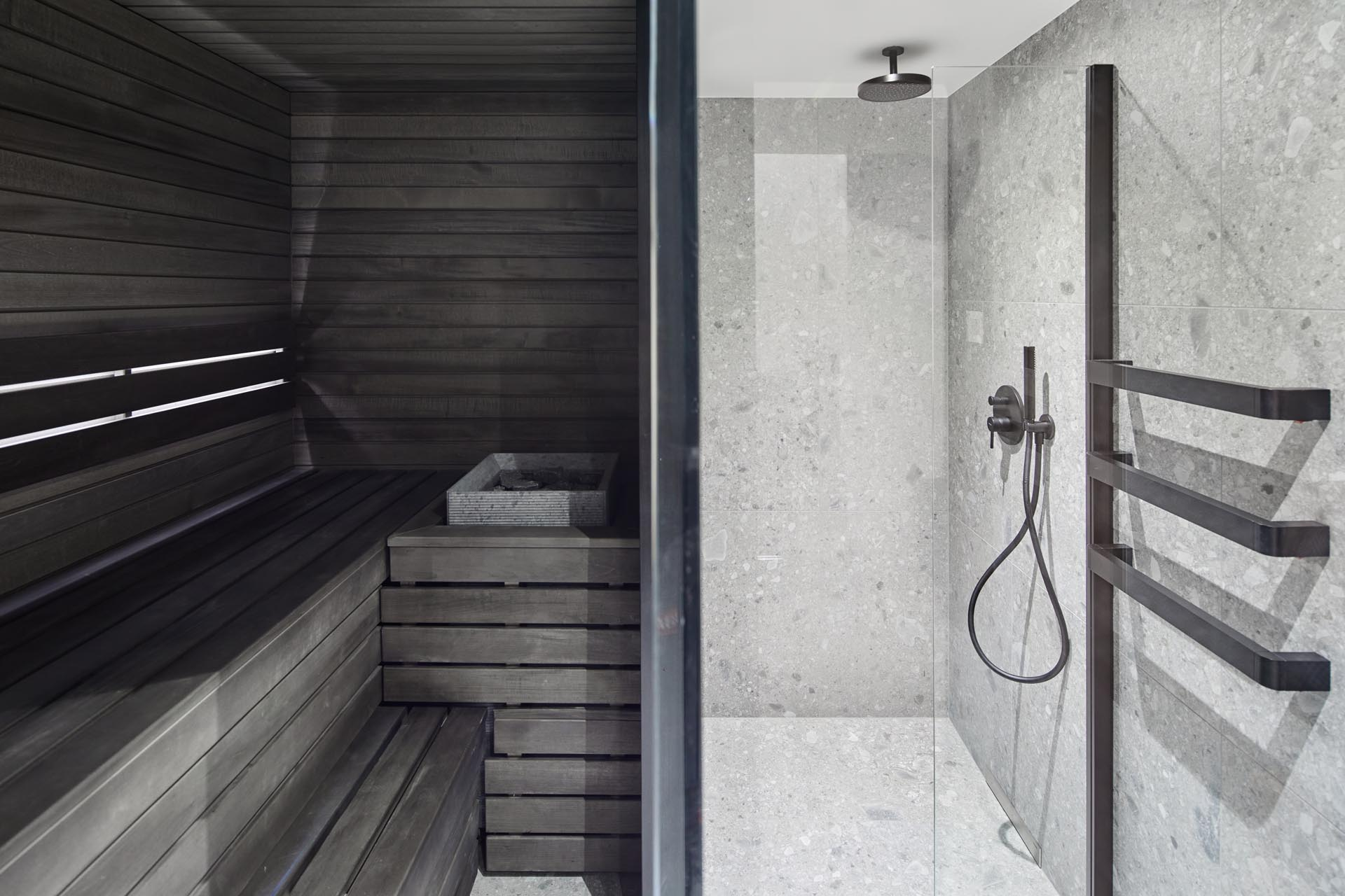 In this modern bathroom, there's blue and dark wood walls, black accents, a walk-in shower, and a sauna.