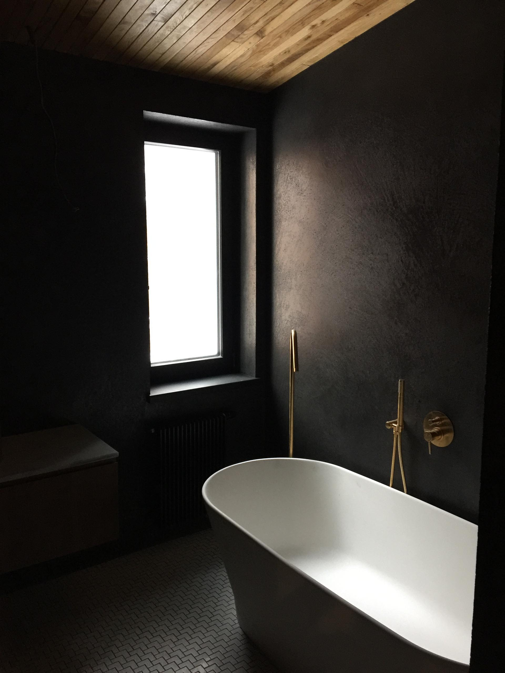 A modern bathroom with black walls, white bathtub, and gold hardware.