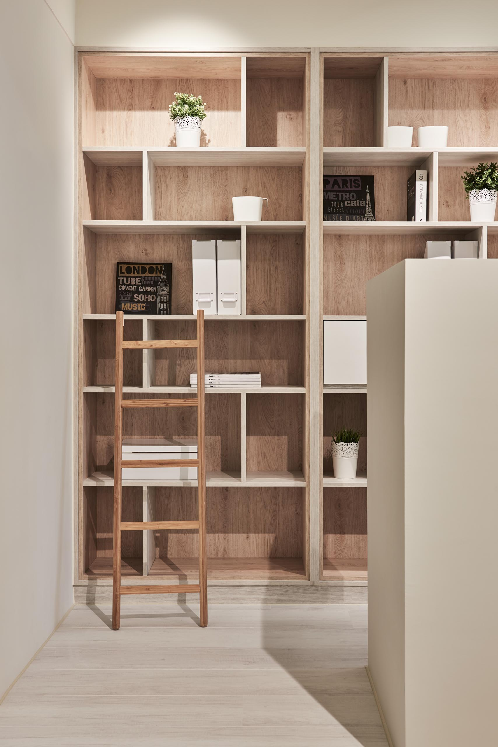 Floor-to-ceiling built-in wood-lined bookshelves provide an abundance of storage for books, folders, plants, and decor items. There's also a small ladder that makes it easy to reach the top shelves.