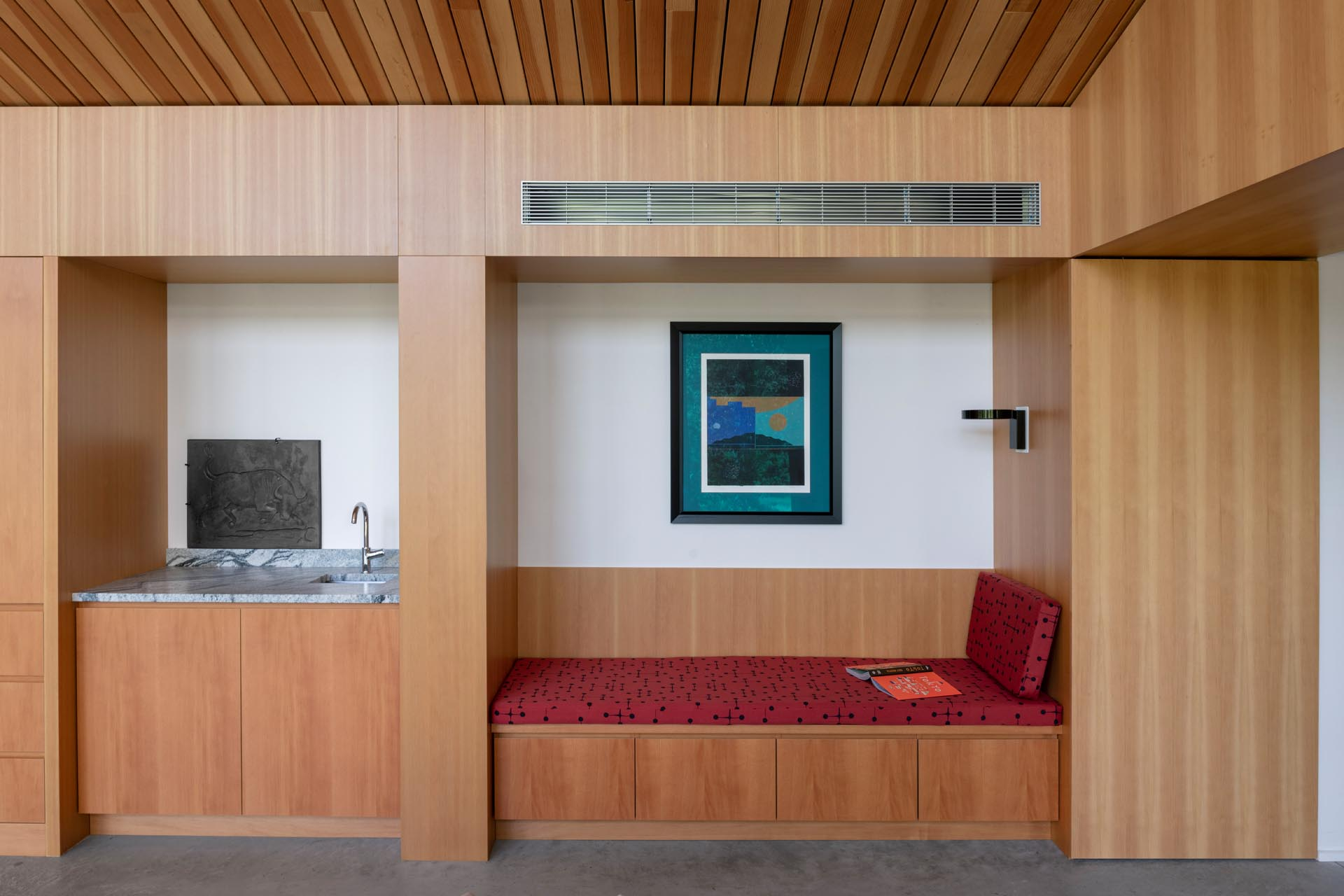 A modern home interior with a built-in bench and small wet bar.
