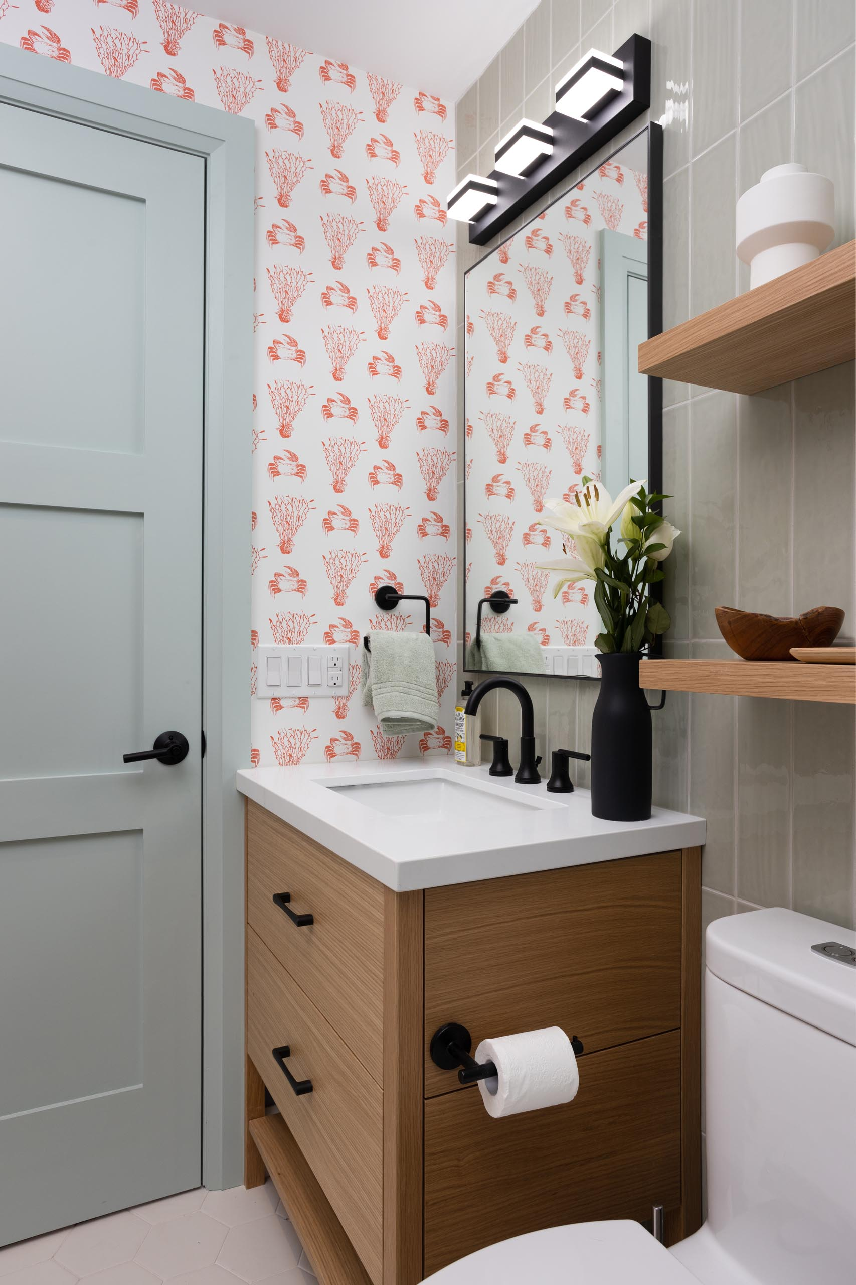 In this bathroom there's black accents and light green tiles that cover the walls, while a wallpaper with a crustacean and coral print adds a quirky colorful touch.