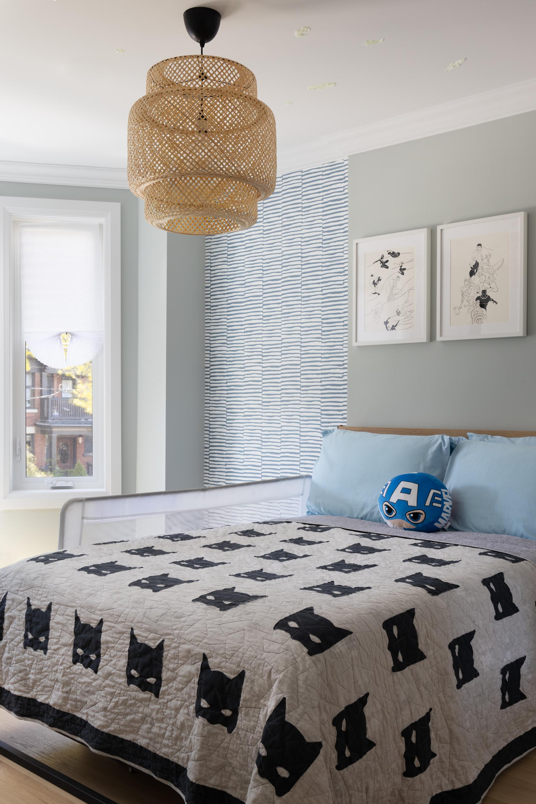 In this contemporary bedroom, there's a woven light fixture, patterned wallpaper, and artwork.