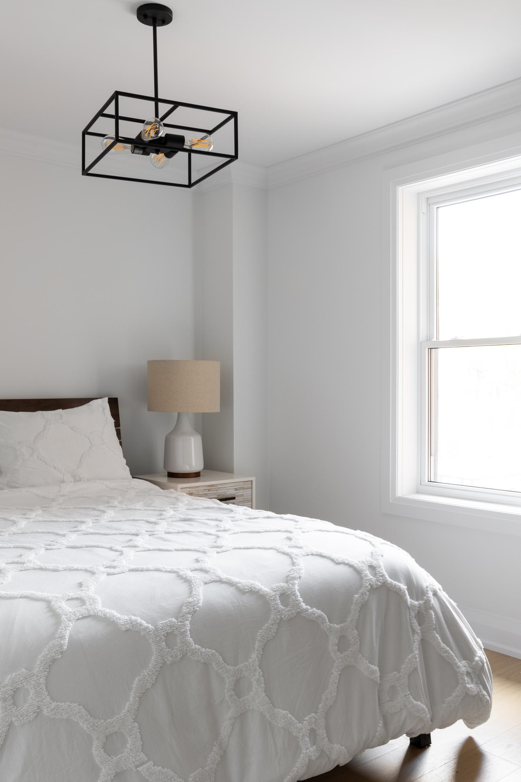 A simple contemporary bedroom design with a minimalist black light fixture that draws the eye upwards to the ceiling.
