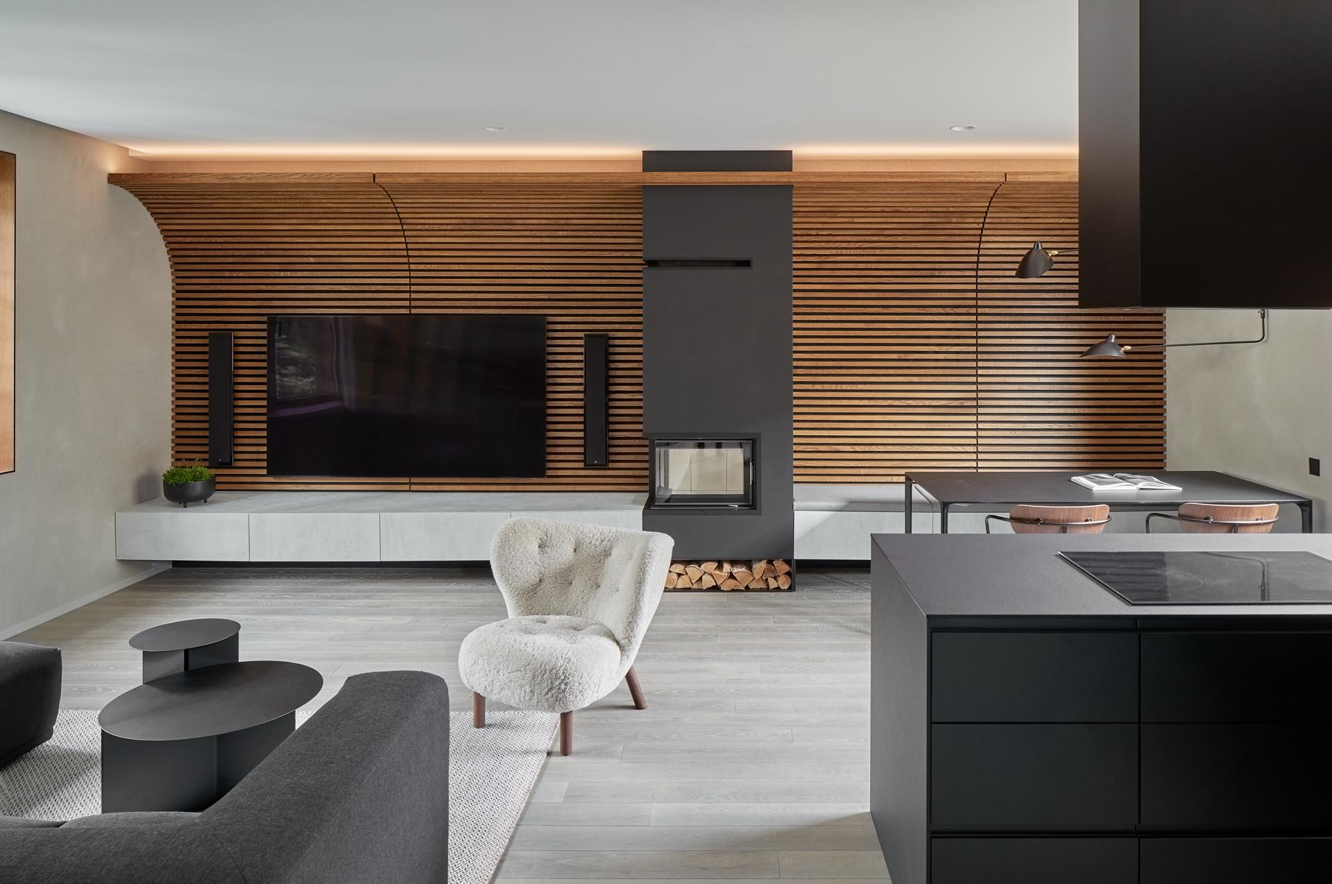 A wood slat accent wall is curved towards the ceiling, and becomes the backdrop for the television and wall-mounted speakers. A fireplace with a black surround that incorporates firewood storage, separates the living room side from the dining area.