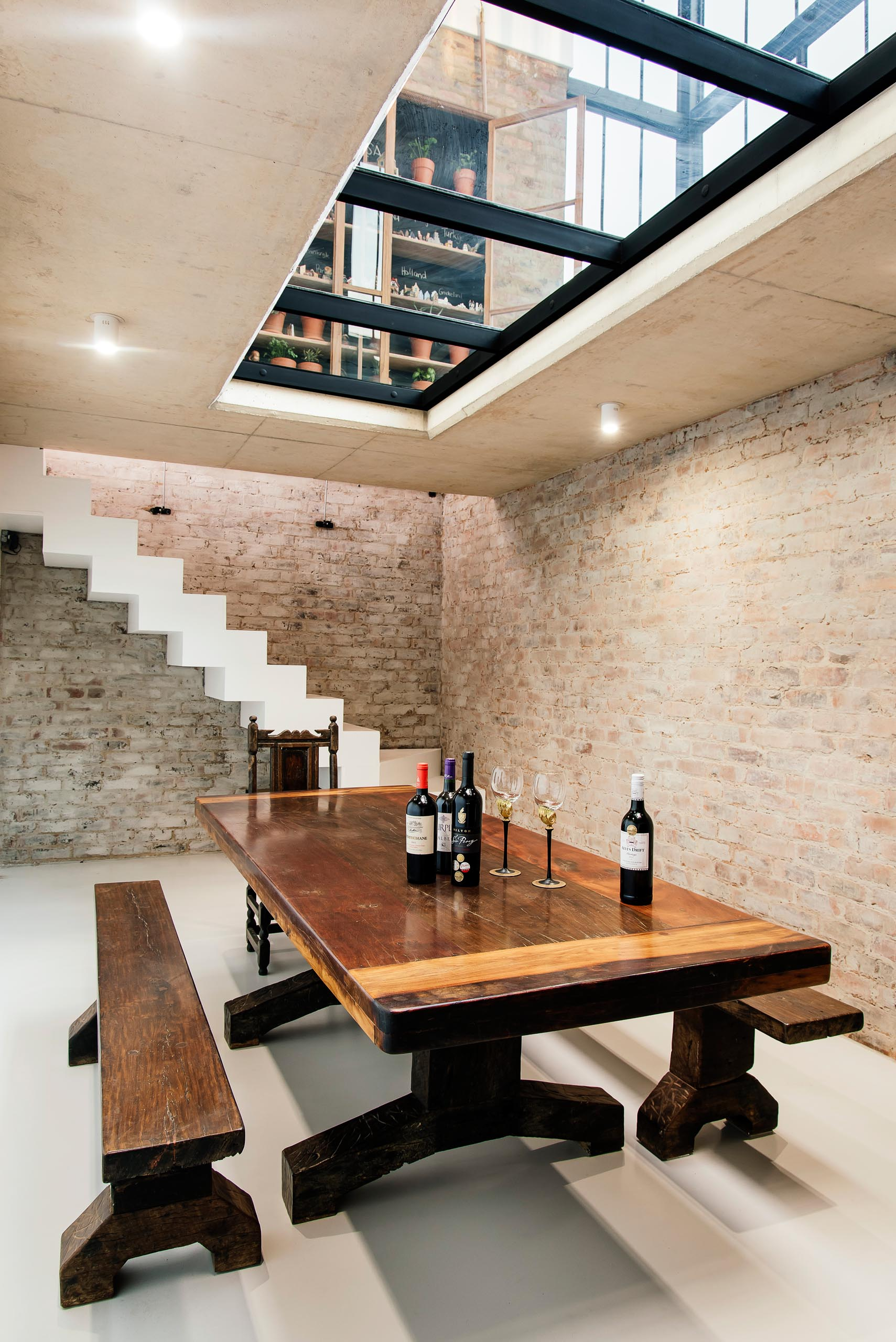 Stairs lead from the conservatory down to the wine cellar via a seamlessly integrated trap door, while a large wood table, which was built by the client, furnishes the room.