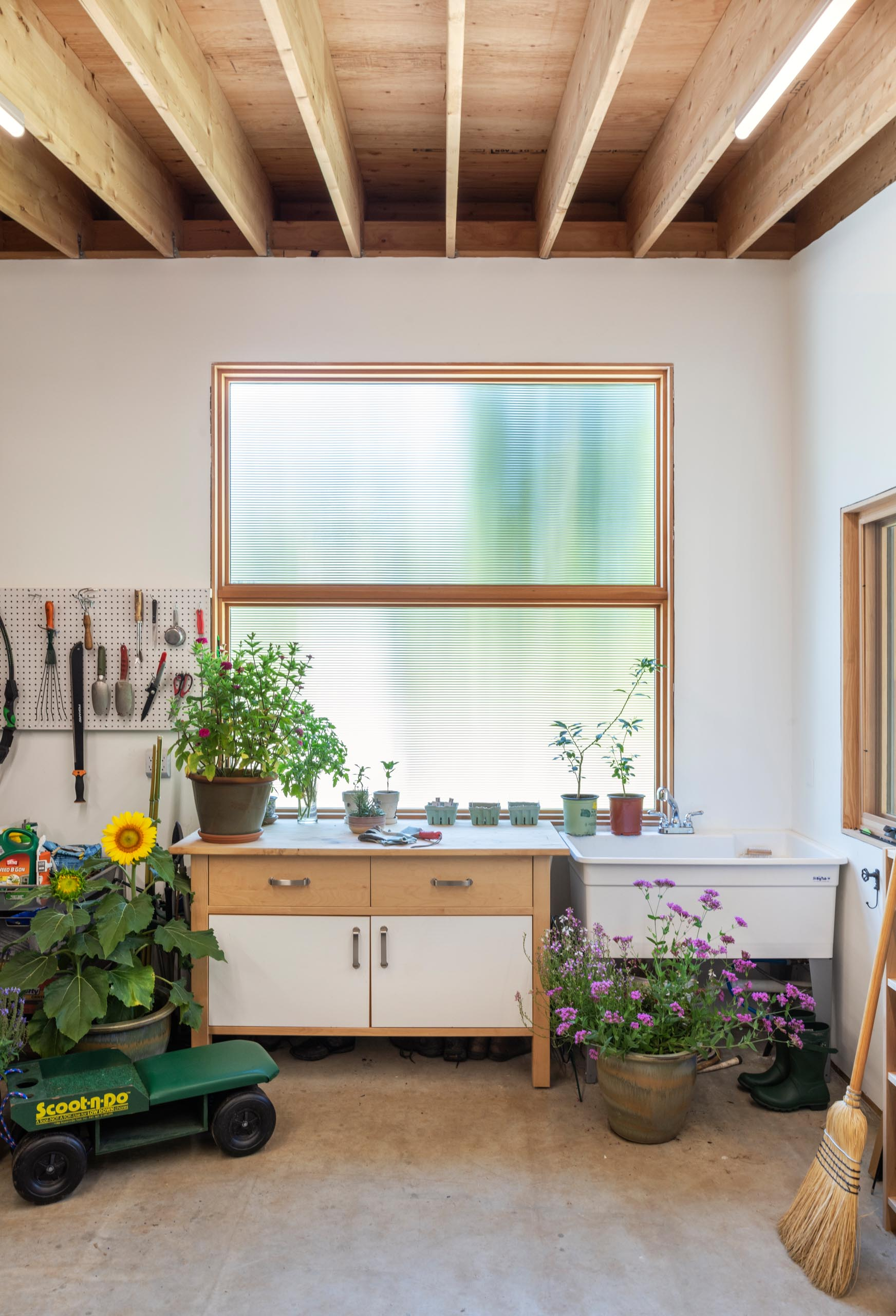 A potting shed with tool storage, work bench and a sink.