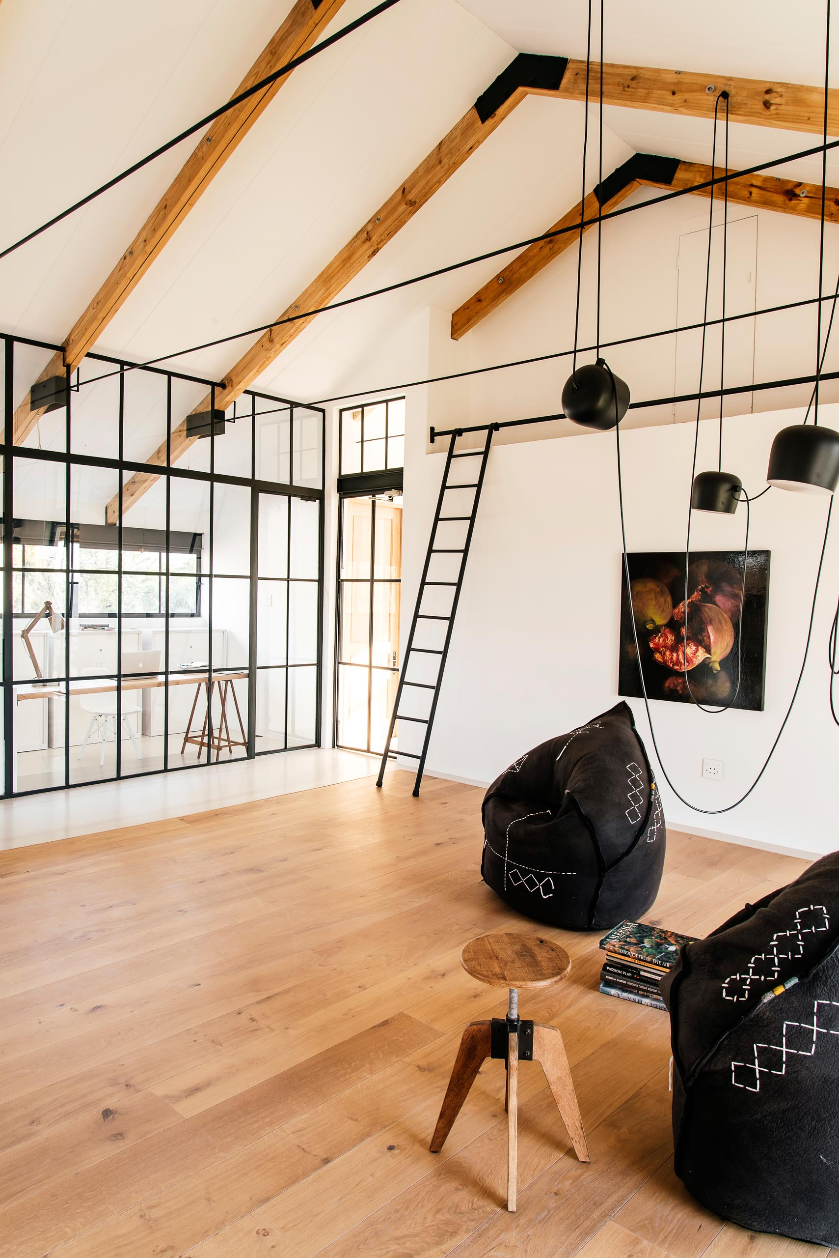 A modern home has a living space with exposed beams, wood flooring, and a pair of black felt chairs.