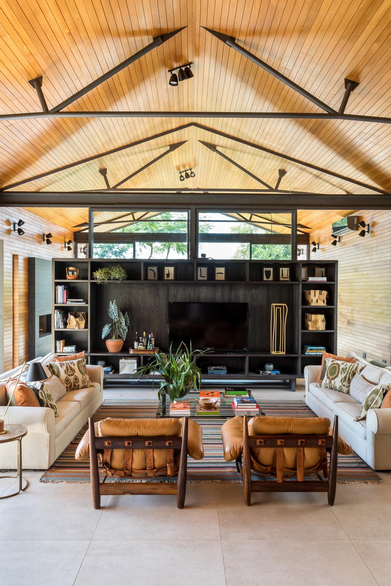 The room divider in this modern home living room, which is made from wood with steel supports, has a wall of shelving with an open area for displaying a television.