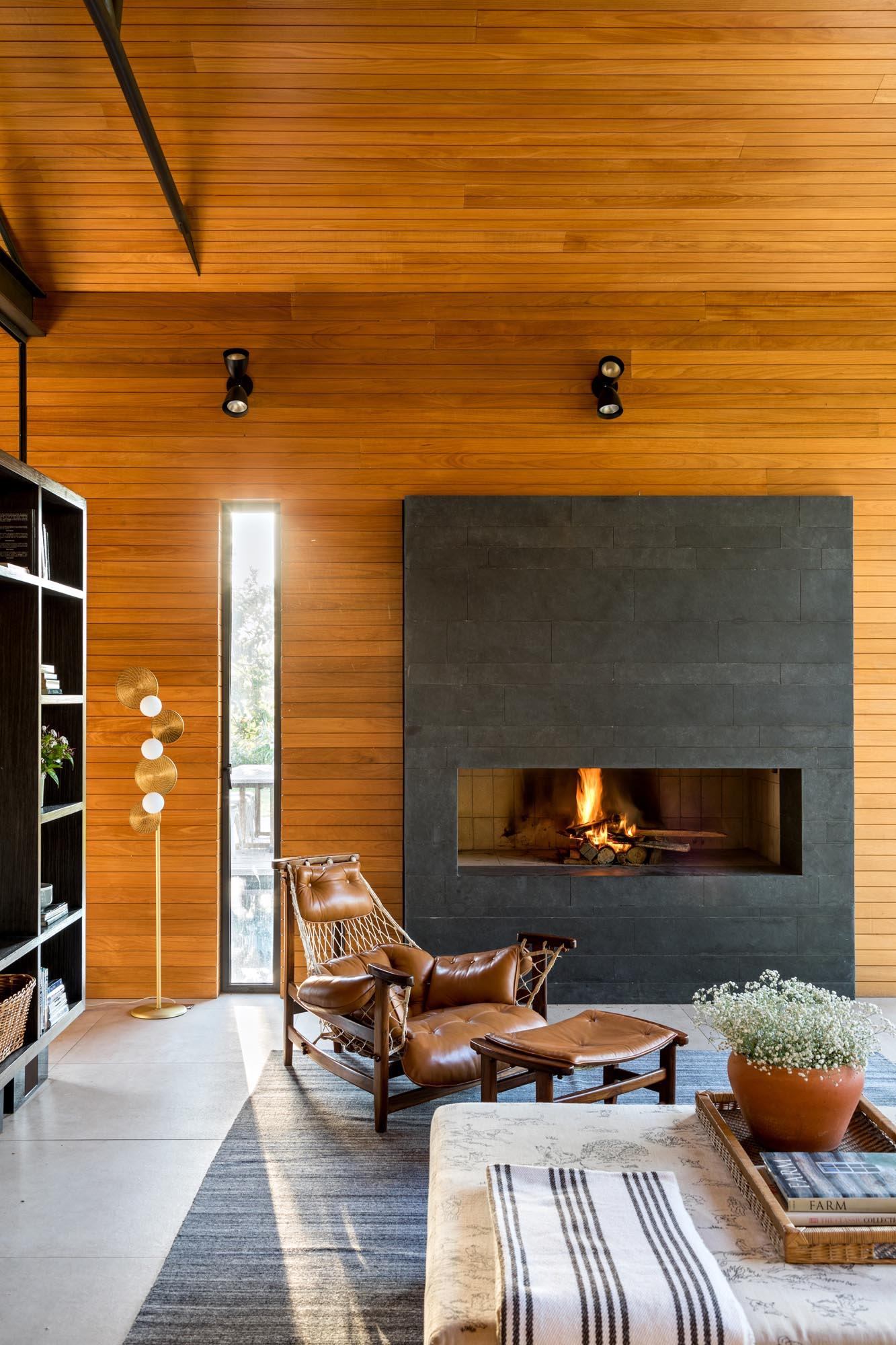 This modern living room is open to the swimming pool, and is furnished with a pair of couches, armchairs, and a fireplace. The room divider is a mirror image of the other side, with shelving and a mounted TV.
