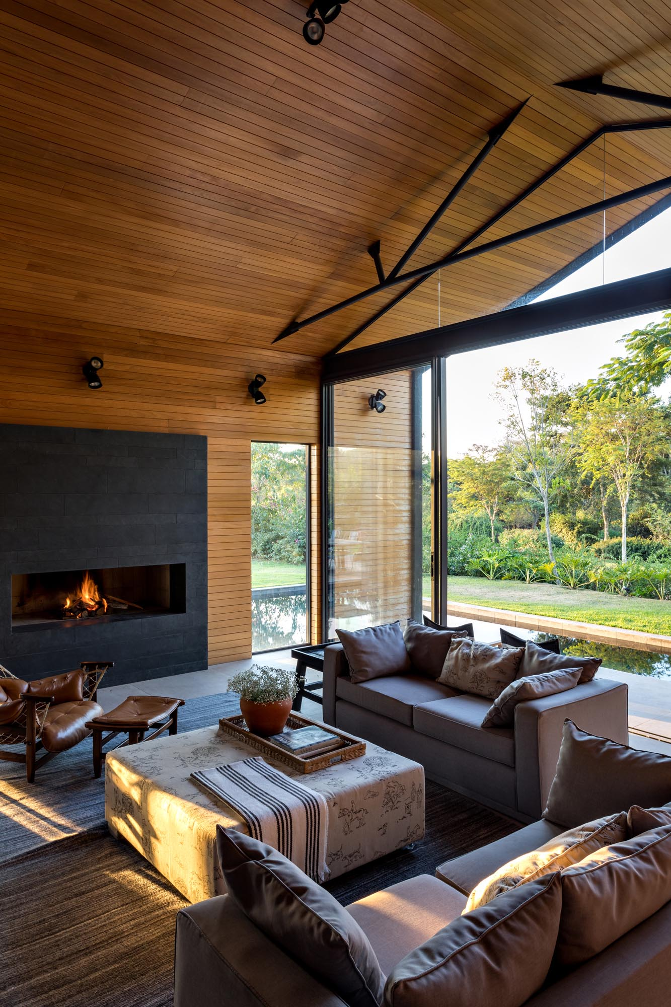 This modern living room is open to the swimming pool, and is furnished with a pair of couches, armchairs, and a fireplace.