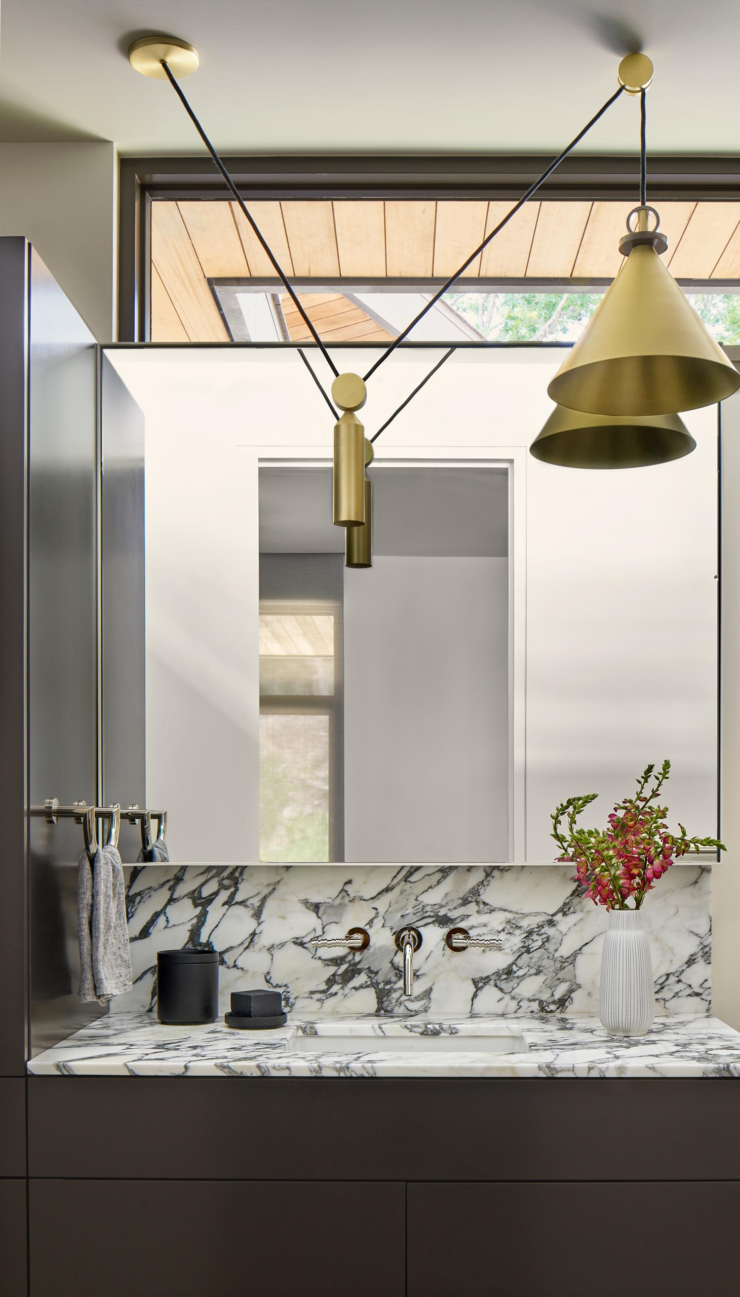 A guest bathroom features a dark vanity with a marbled top and metallic lighting.