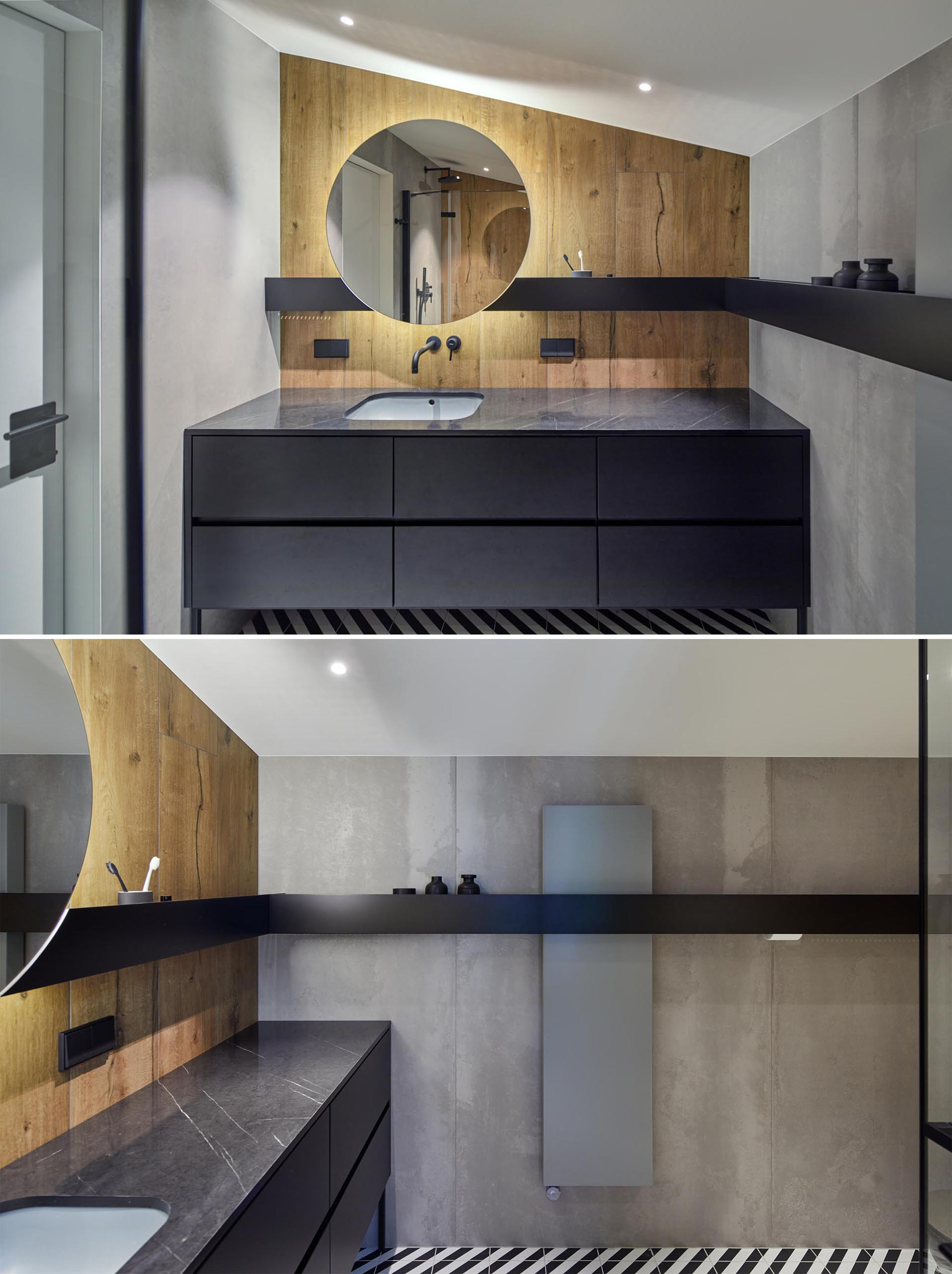 In this modern bathroom, there's a wood accent wall, backlit round mirror, and a black shelf that wraps around the room.