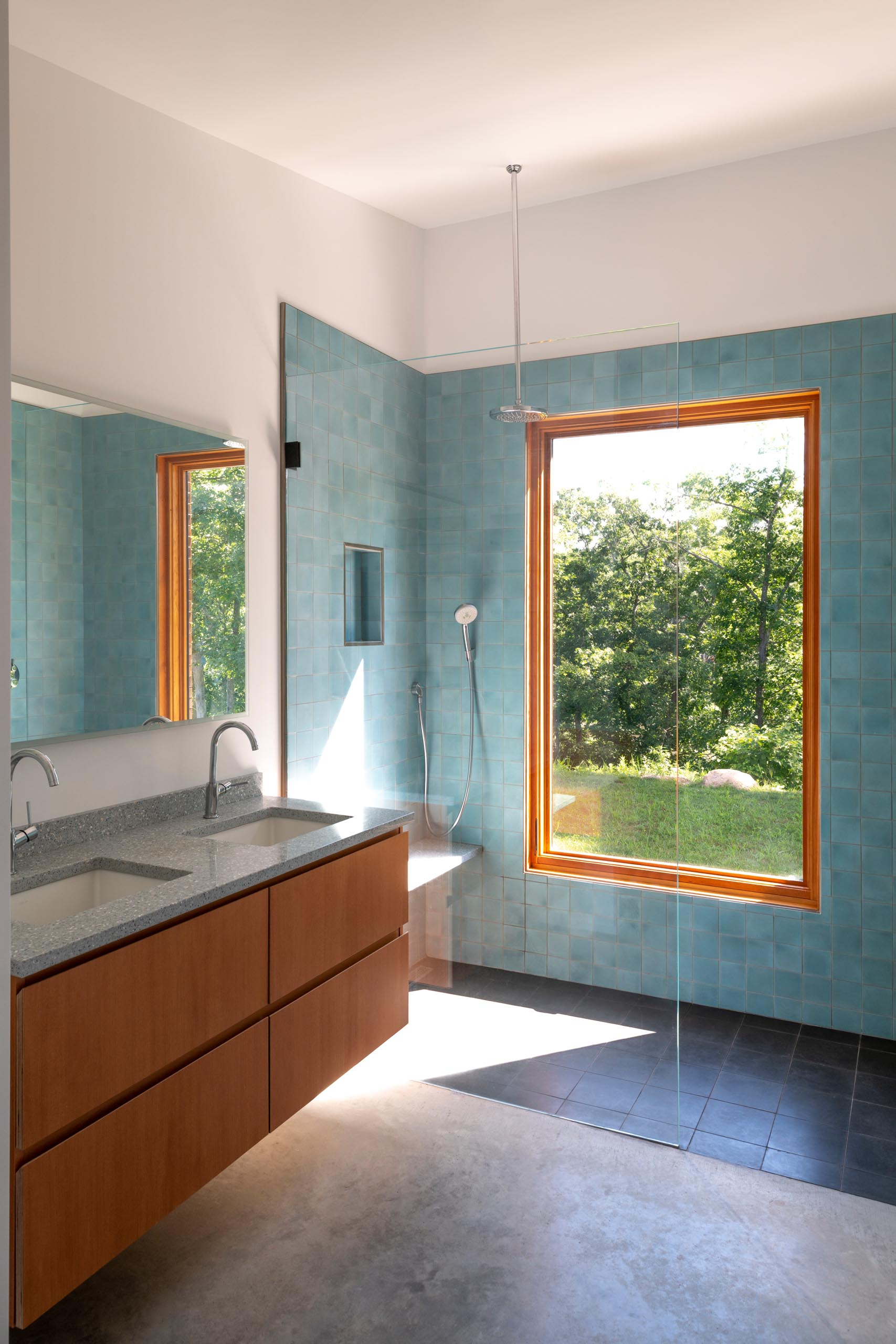 A modern bathroom with square blue accent tiles that covered the shower walls.