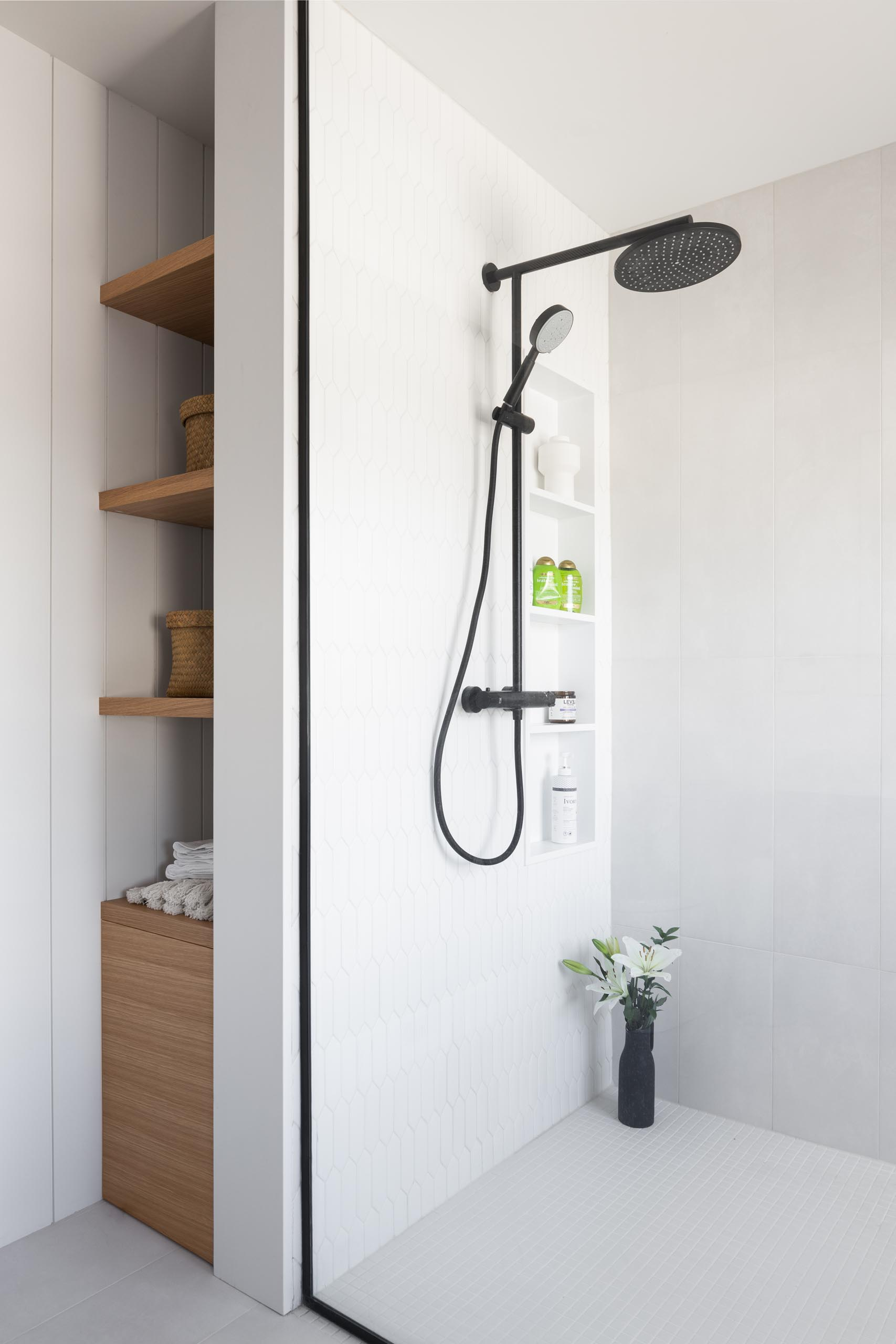 A modern bathroom with white picket-style tiles, a shelving niche, and built-in wood shelves.