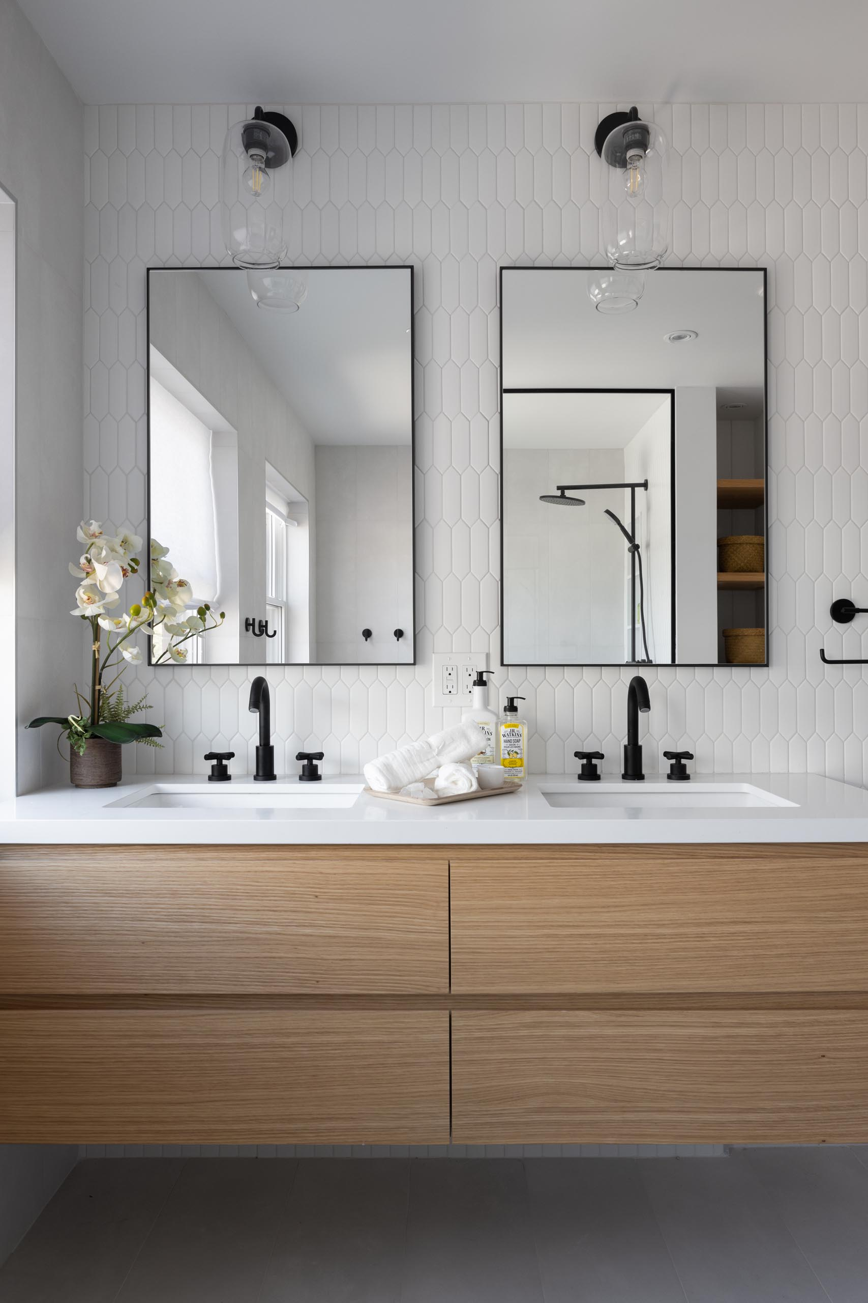 This modern bathroom includes a picket-style tile installation on the wall, a wood vanity with double sinks and black framed mirrors.