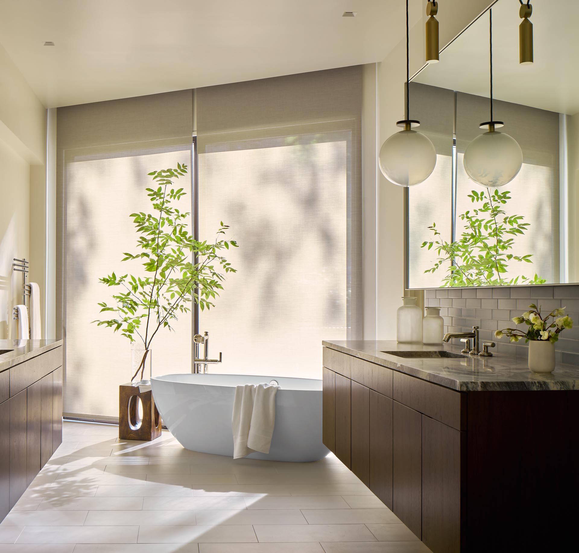 In this modern primary bathroom, there's dual vanities and a freestanding bathtub by the windows.