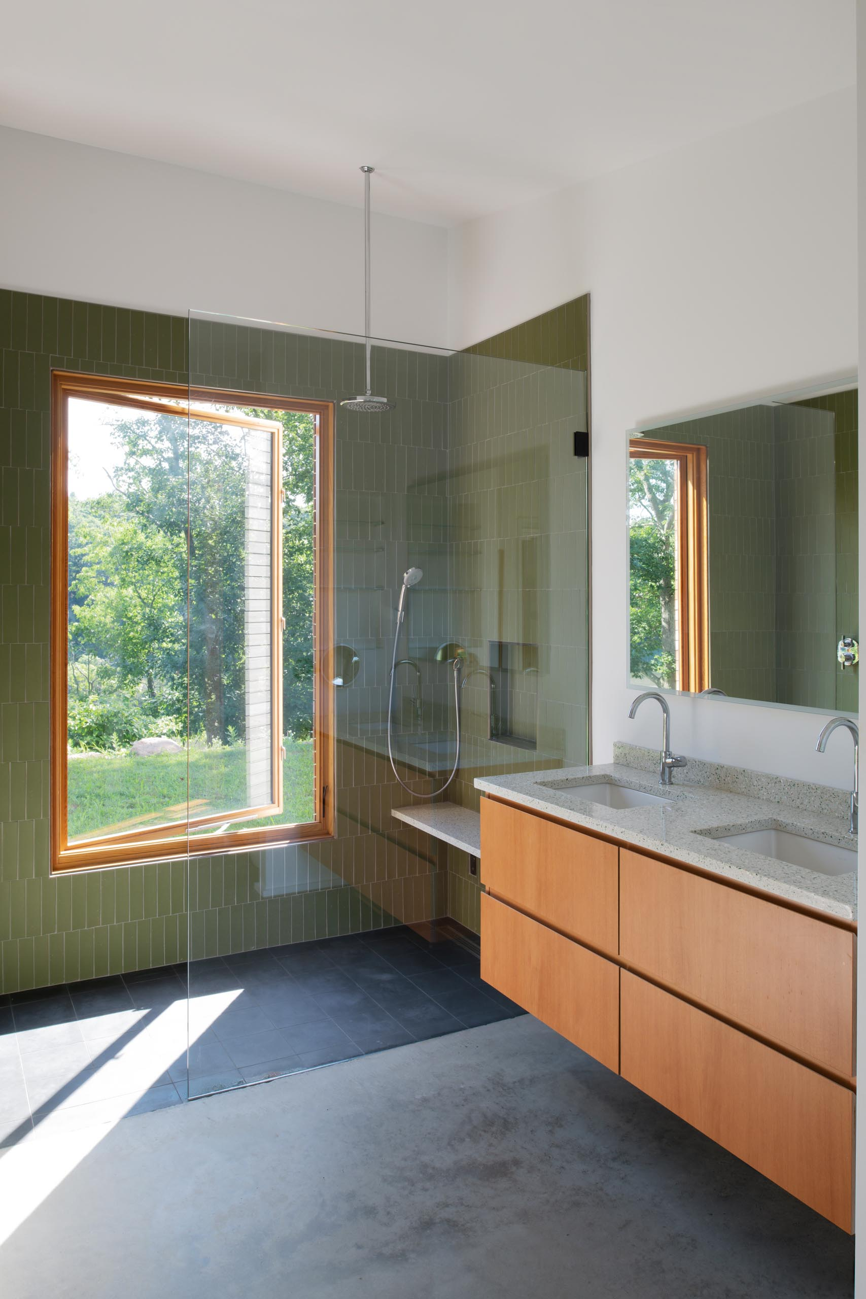 A modern bathroom with green accent tiles that covered the shower walls.