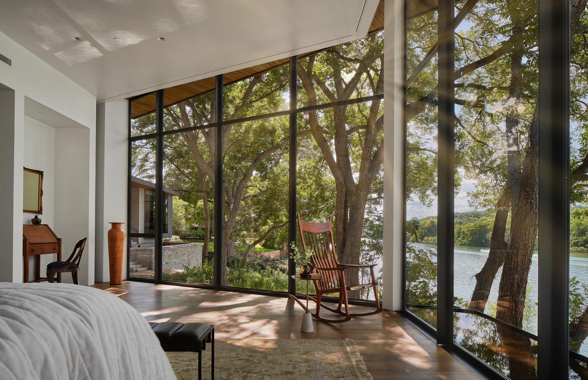 This primary bedroom has a hexagonal layout and 180 degree views of the lake through the floor-to-ceiling windows.