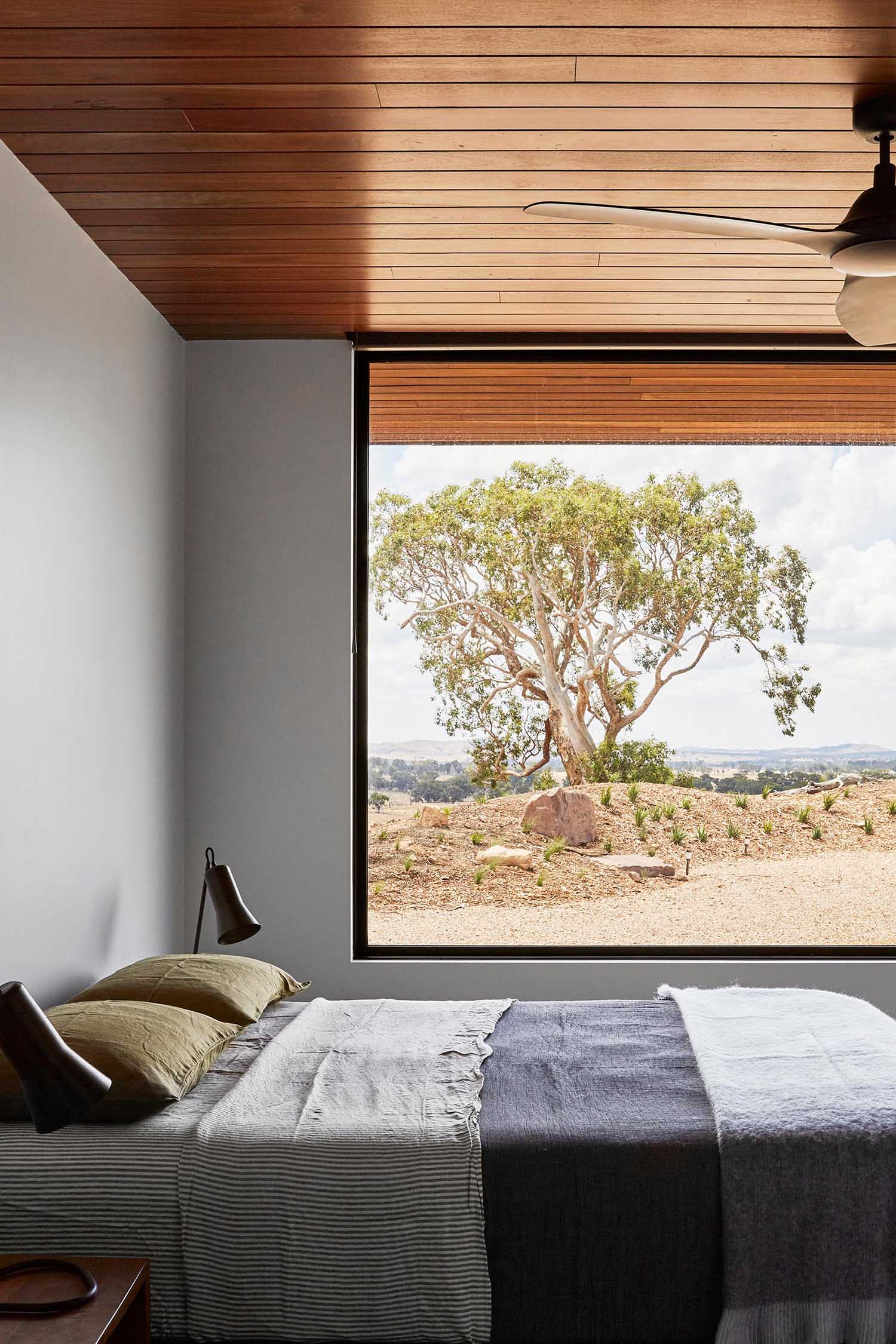 In this modern bedroom, a large picture window with a black frame perfectly showcases the rural landscape.