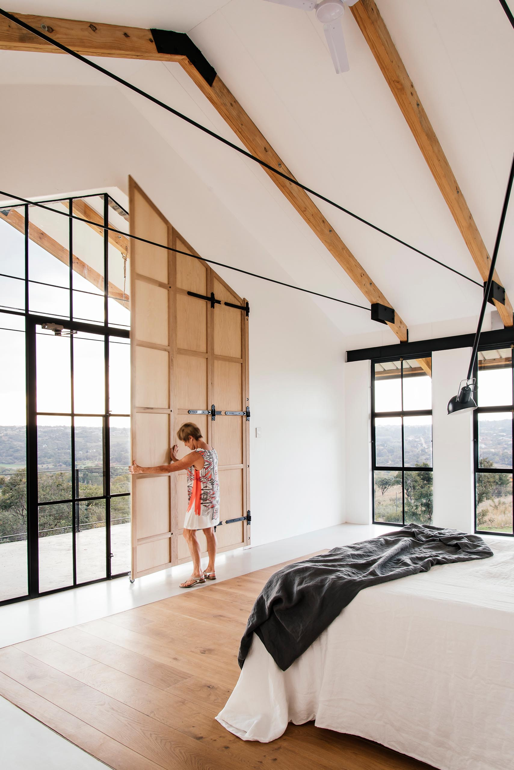 This primary bedroom is minimally furnished and positioned to enjoy bird watching into the tree canopy and sunset views. The large overhanging patio and timber shutters assist in eliminating unwanted afternoon sun.