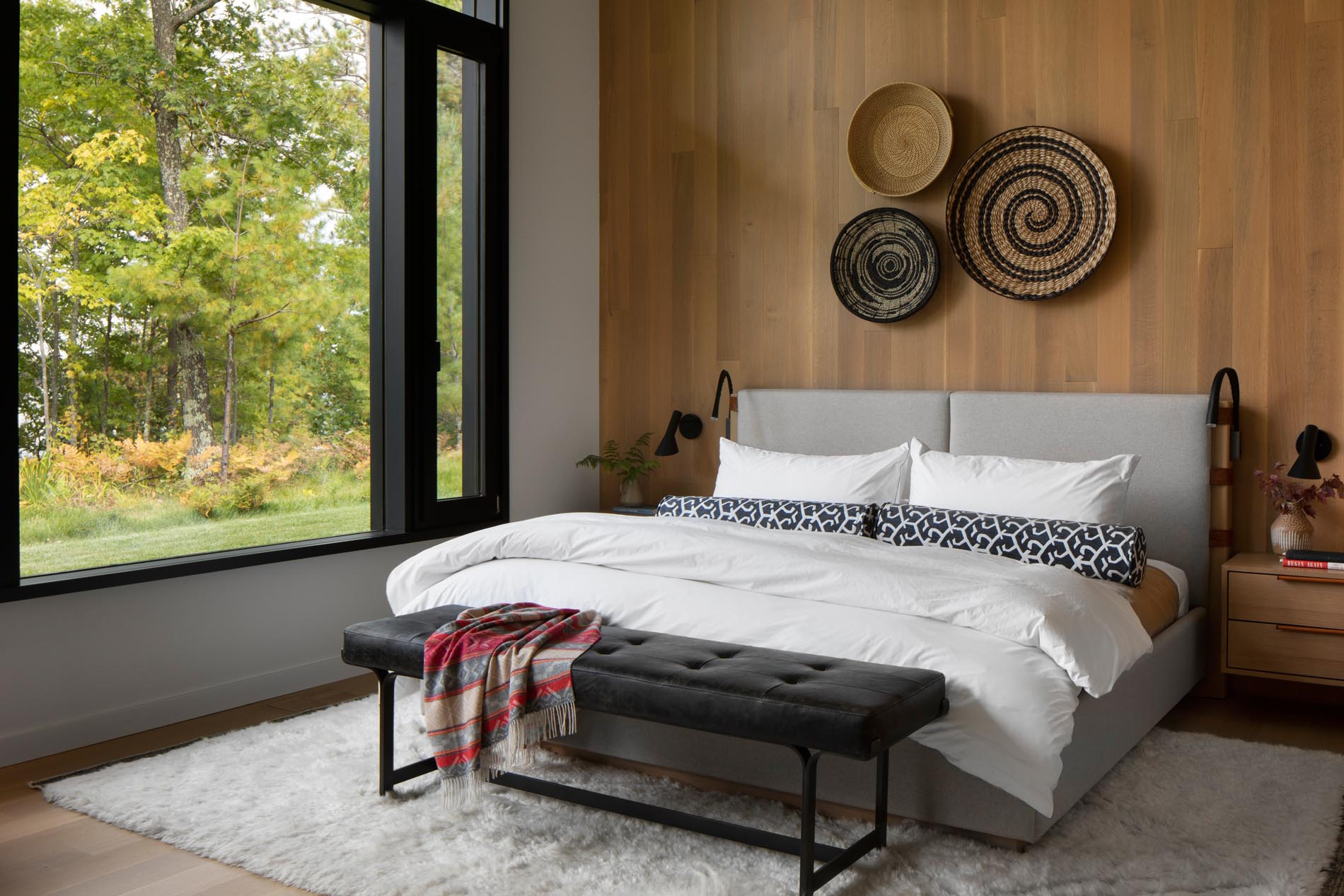 This modern bedroom has a floor-to-ceiling wood accent wall adorned with woven baskets, provides a backdrop for an upholstered gray bed.